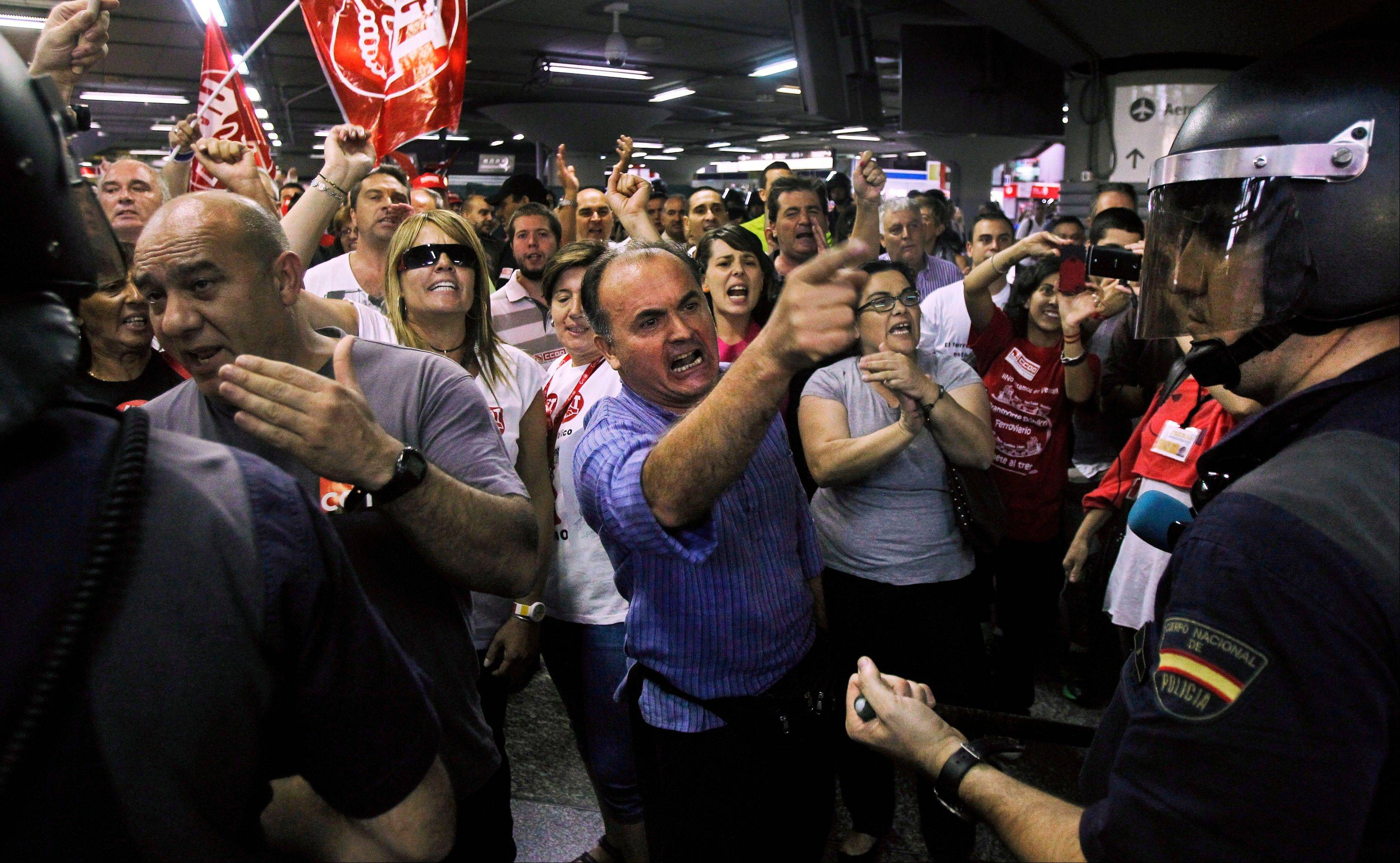 Rail workers protest as police riots stand guard at Atocha station, Madrid, during a partial national rail strike, Monday. Hundreds of Spanish train services have been canceled as rail and subway workers staged strikes to protest wage cuts and reforms.
