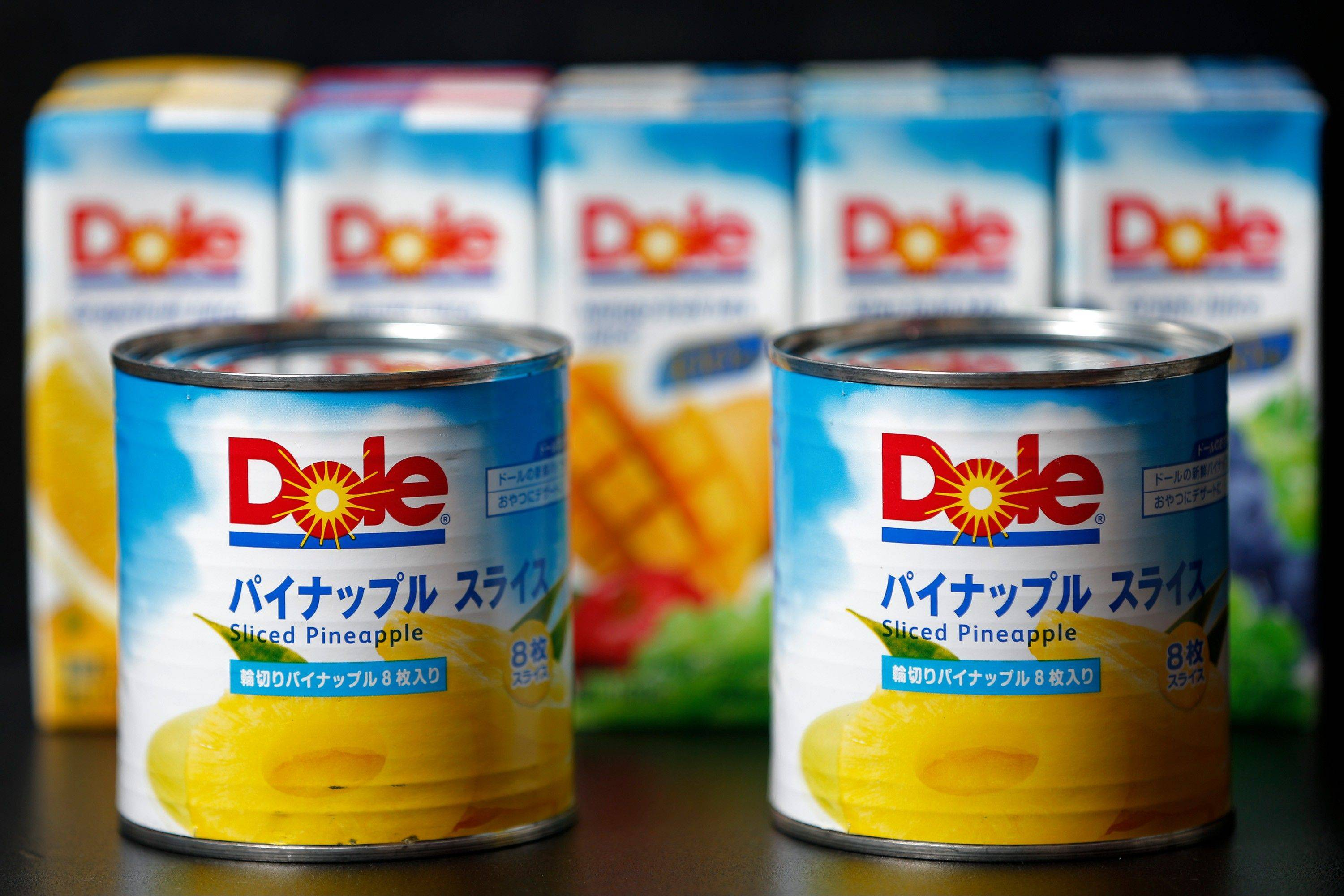 9 Cans of Dole Food Co. sliced pineapple in front of cartons of the company's fruit juice in Soka City, Saitama Prefecture, Japan.