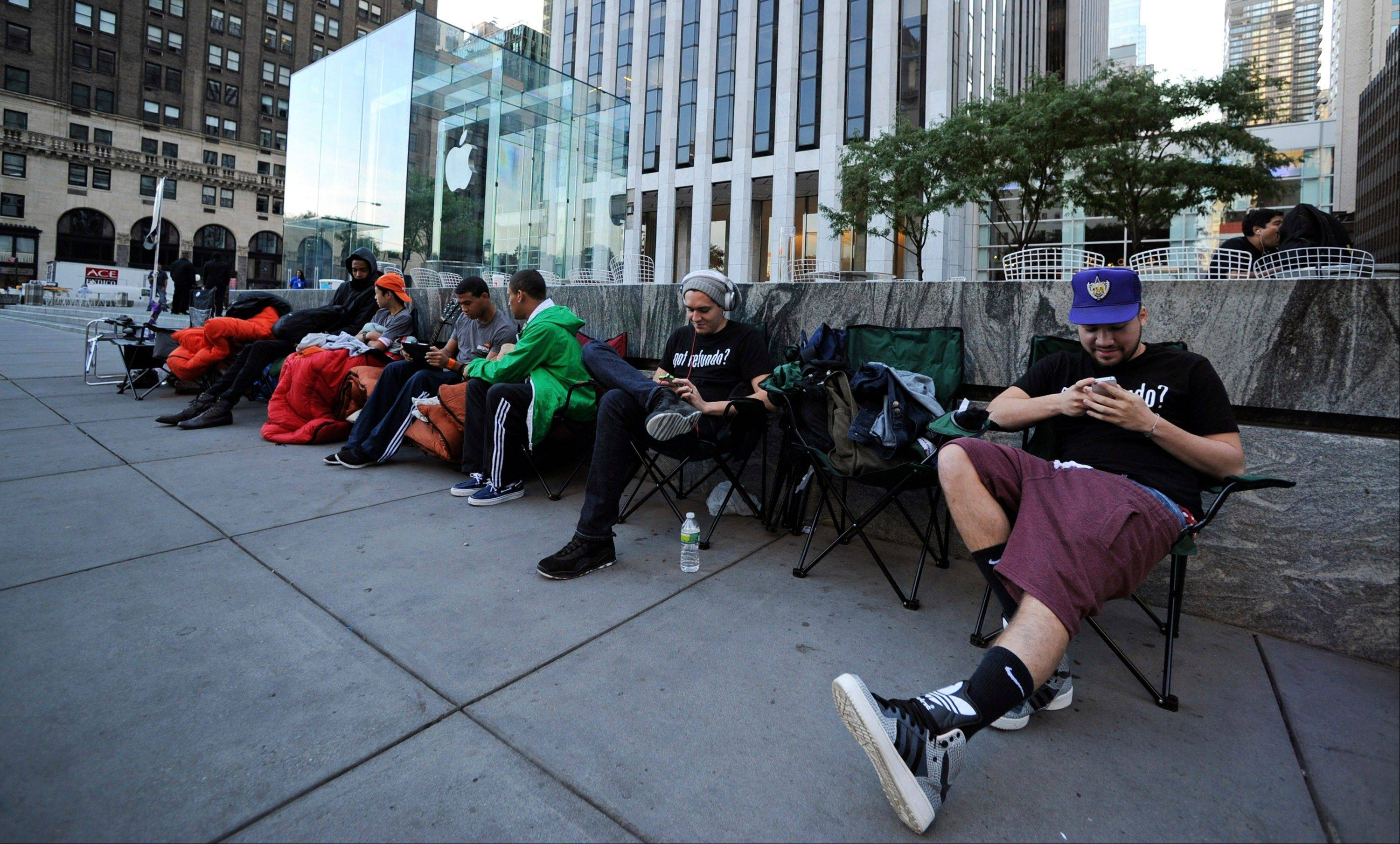 People line up in front of the Apple Inc. store on Fifth Avenue in advance of the sale of the iPhone 5 in New York, U.S. Monday.