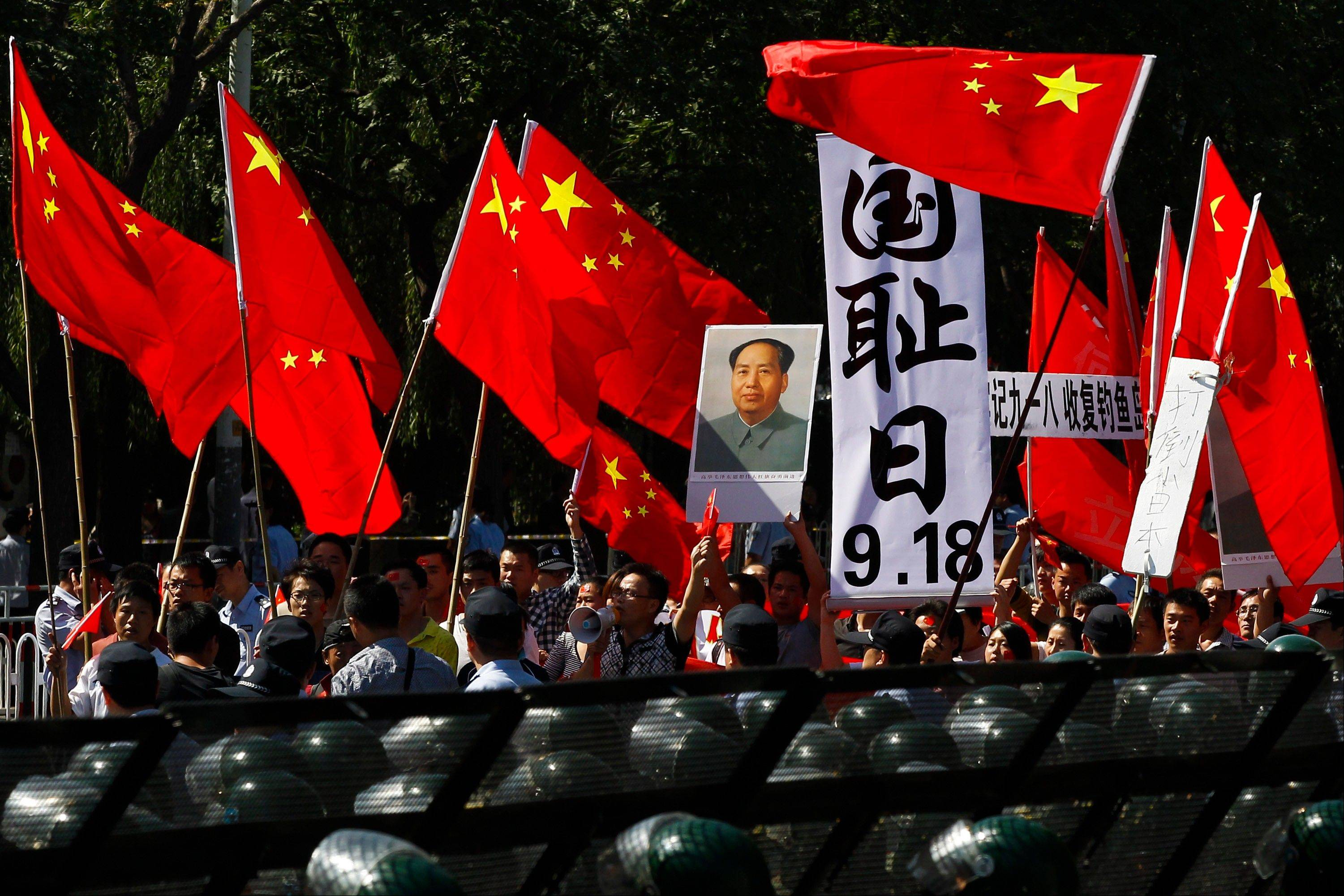 "Anti-Japan protesters hold portraits of the late Communist leader Mao Zedong, Chinese national flags, and a poster that reads: ""Sept. 18, National Humiliation Day,"" while marching on a street outside the Japanese Embassy in Beijing Tuesday, Sept. 18, 2012. The 81st anniversary of a Japanese invasion brought a fresh wave of anti-Japan demonstrations in China on Tuesday, with thousands of protesters venting anger over the colonial past and a current dispute involving contested islands in the East China Sea."