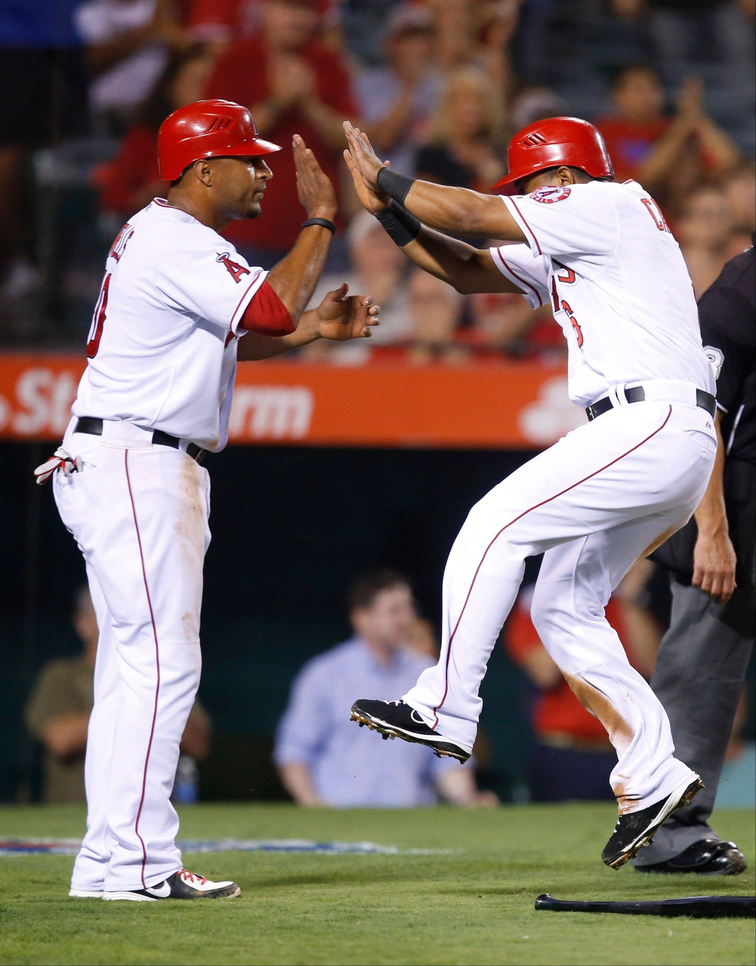 The Angels' Vernon Wells, left, and Alberto Callaspo celebrate after they scored on a single by Chris Iannetta in the fourth inning Tuesday at home against the Rangers.
