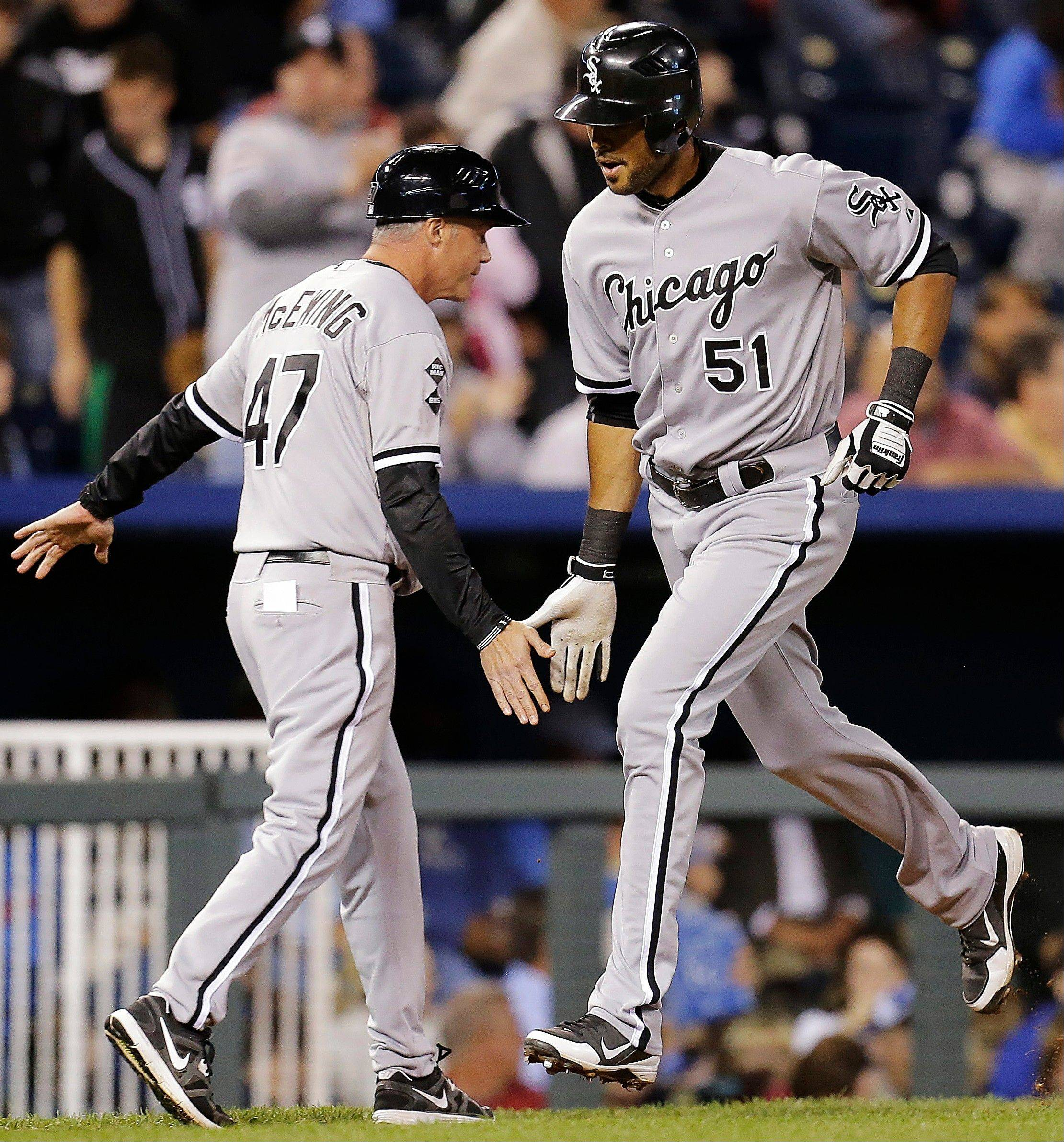 The White Sox' Alex Rios celebrates with third-base coach Joe McEwing after hitting a solo home run during the seventh inning Tuesday night at Kansas City.