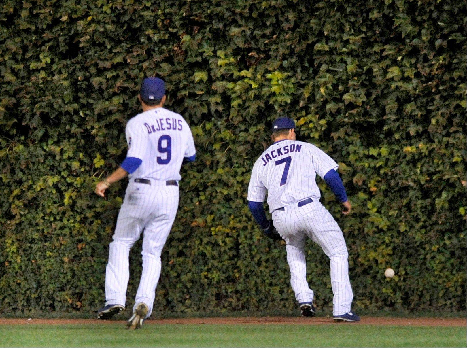 Cubs center fielder Brett Jackson right, chases down a 3-run double by Cincinnati Reds' Ryan Hanigan as right fielder David DeJesus left, watches during the sixth inning of a baseball game in Chicago, Tuesday, Sept. 18, 2012.