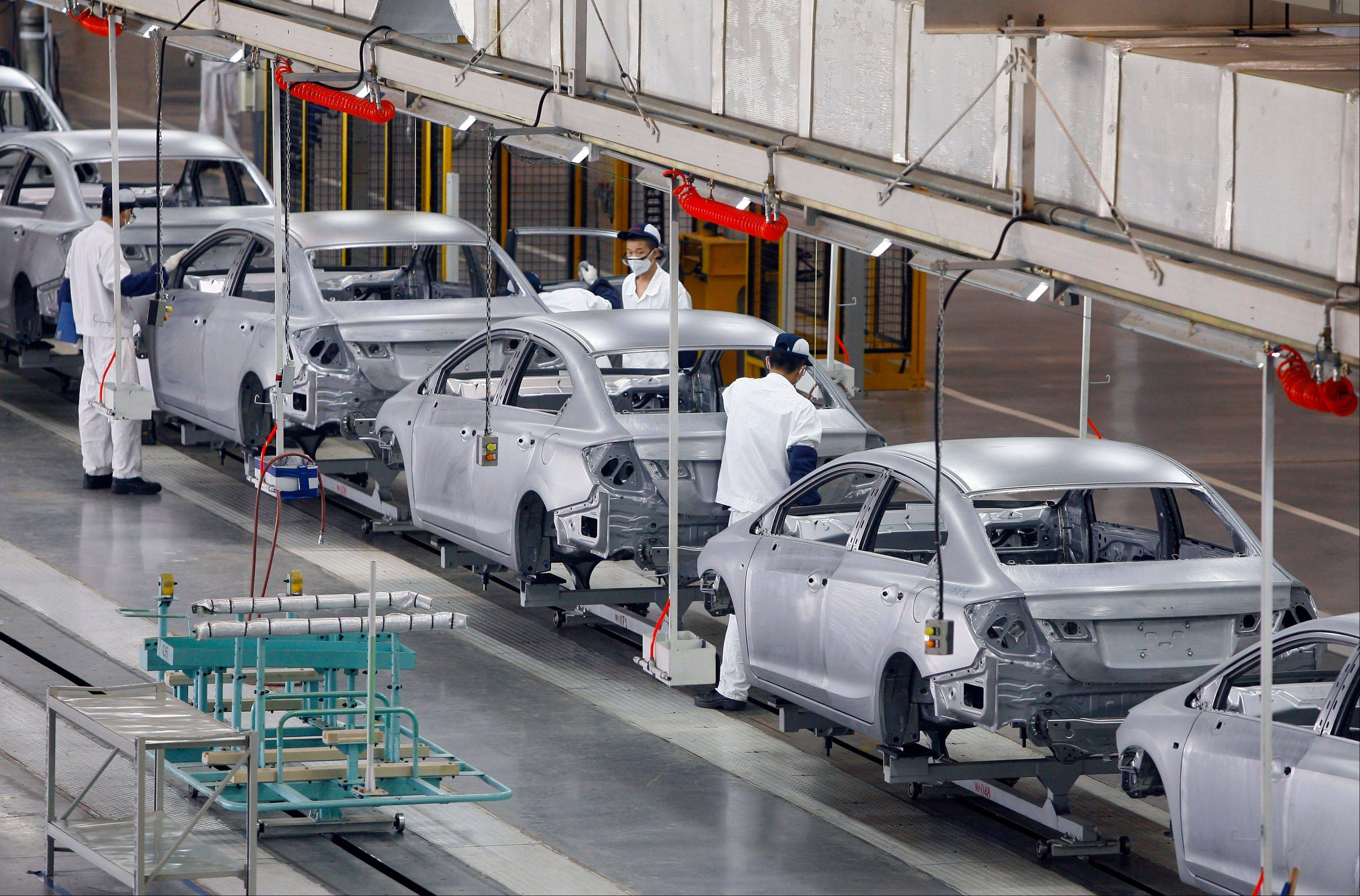 Chinese workers assemble cars at a plant of Dongfeng Honda, a joint venture between China's Dongfeng Motor and Japan's Honda Motor in Wuhan in central China's Hubei province.