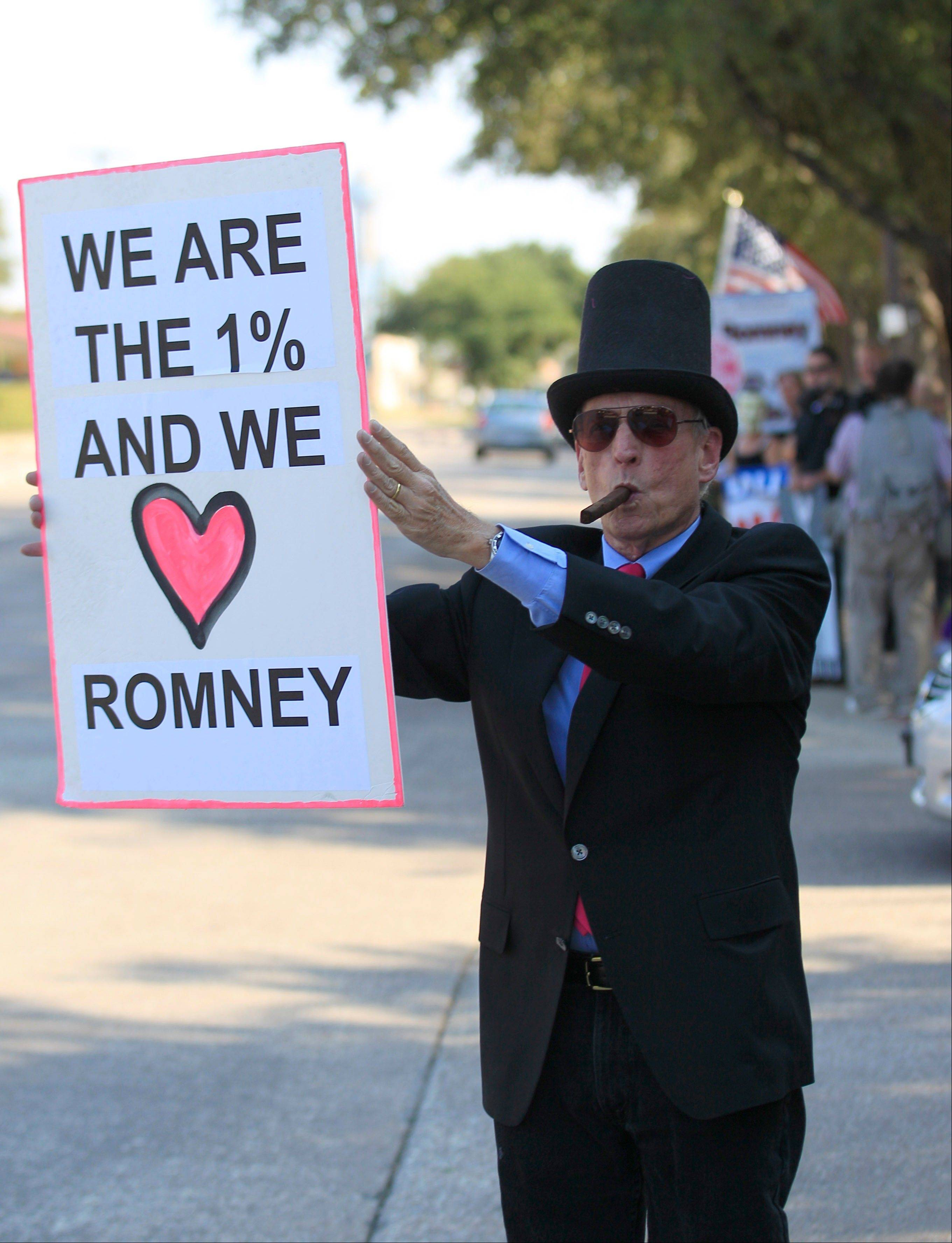 Using street theater, Grant Youngman holds a sign as he protests outside the hotel hosting a fundraiser for Republican presidential candidate and former Massachusetts Gov. Mitt Romney in Dallas, Tuesday.