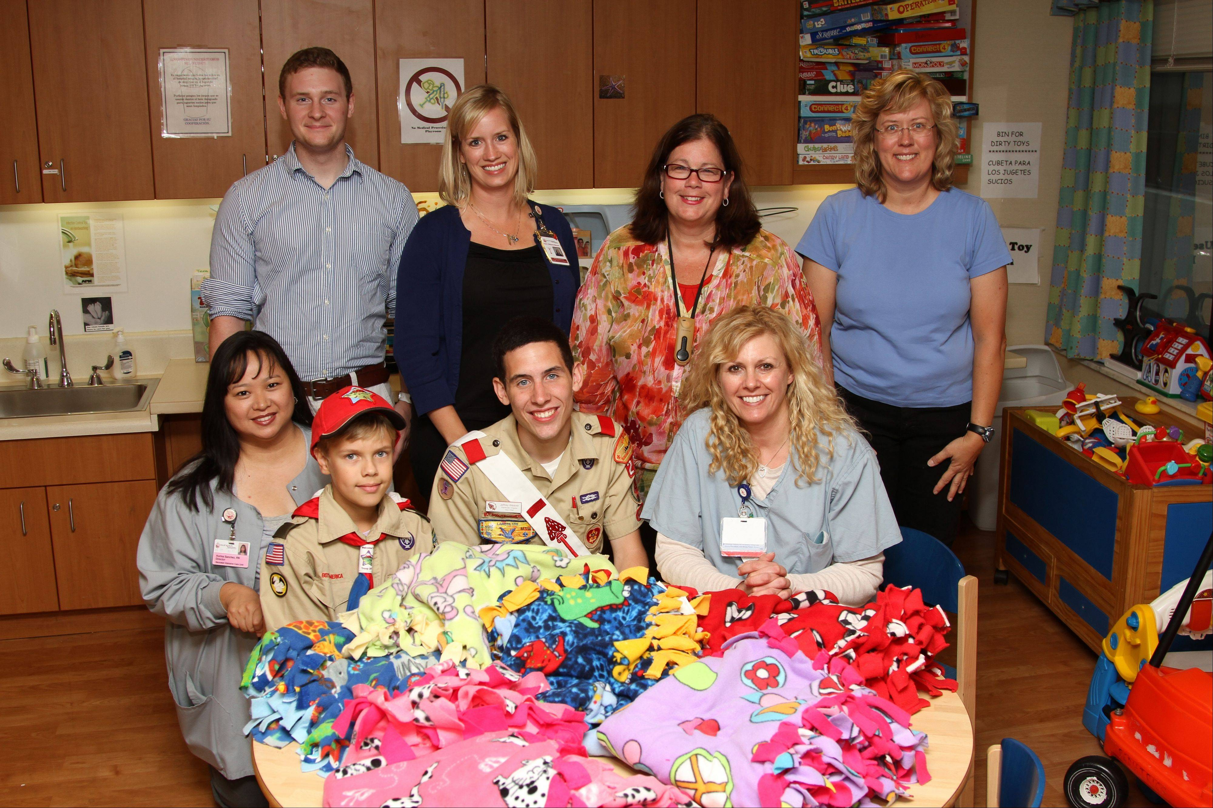 Eagle Scout candidate Jeffery Weaver and a fellow Boy Scout present homemade fleece blankets to the Pediatric Unit staff at St. Alexius Medical Center in Hoffman Estates.