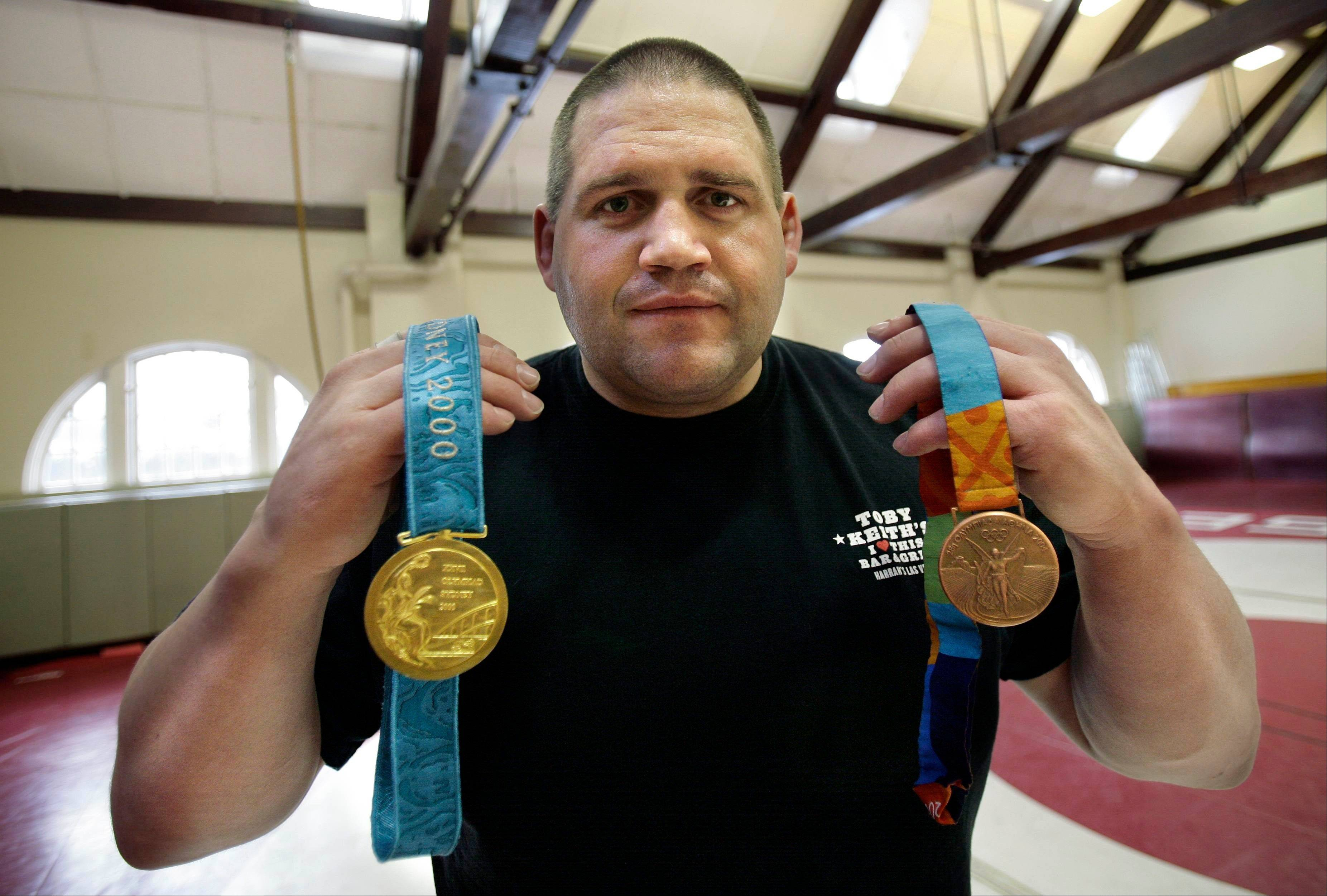 Rulon Gardner holds his gold and bronze Olympic medals after giving a motivational talk to students and faculty at the Middlesex School in Concord, Mass., on Feb. 27, 2007.
