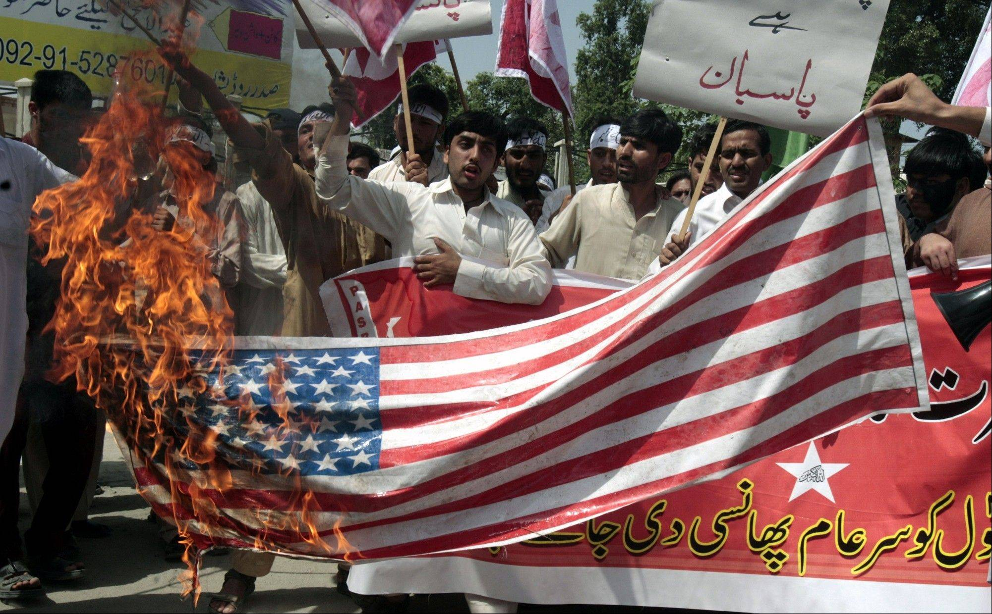 Pakistani protesters burn a representation of a U.S. flag during a demonstration that is part of widespread anger across the Muslim world about a film ridiculing Islam's Prophet Muhammad, near the US consulate in Peshawar, Pakistan, Tuesday, Sept. 18, 2012.