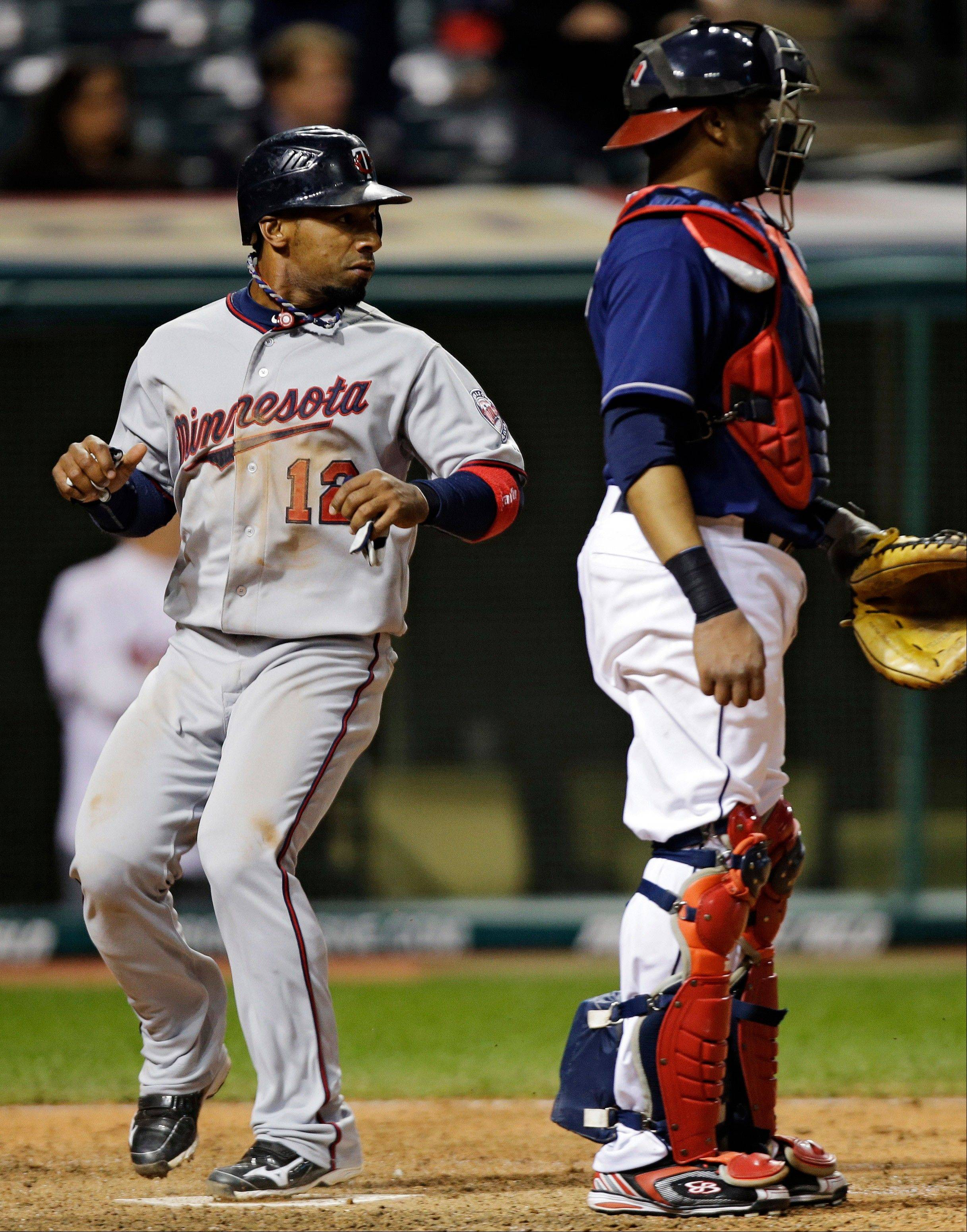 Minnesota's Alexi Casilla and Indians catcher Carlos Santana look toward third base after Casilla scored on a single by Pedro Florimon in the 12th inning Tuesday in Cleveland.