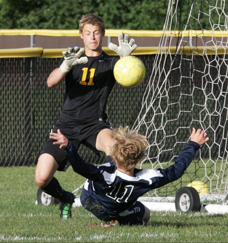 Carmel goalie Michael Zucco blocks a shot by St. Viator midfielder Jackson Owens.