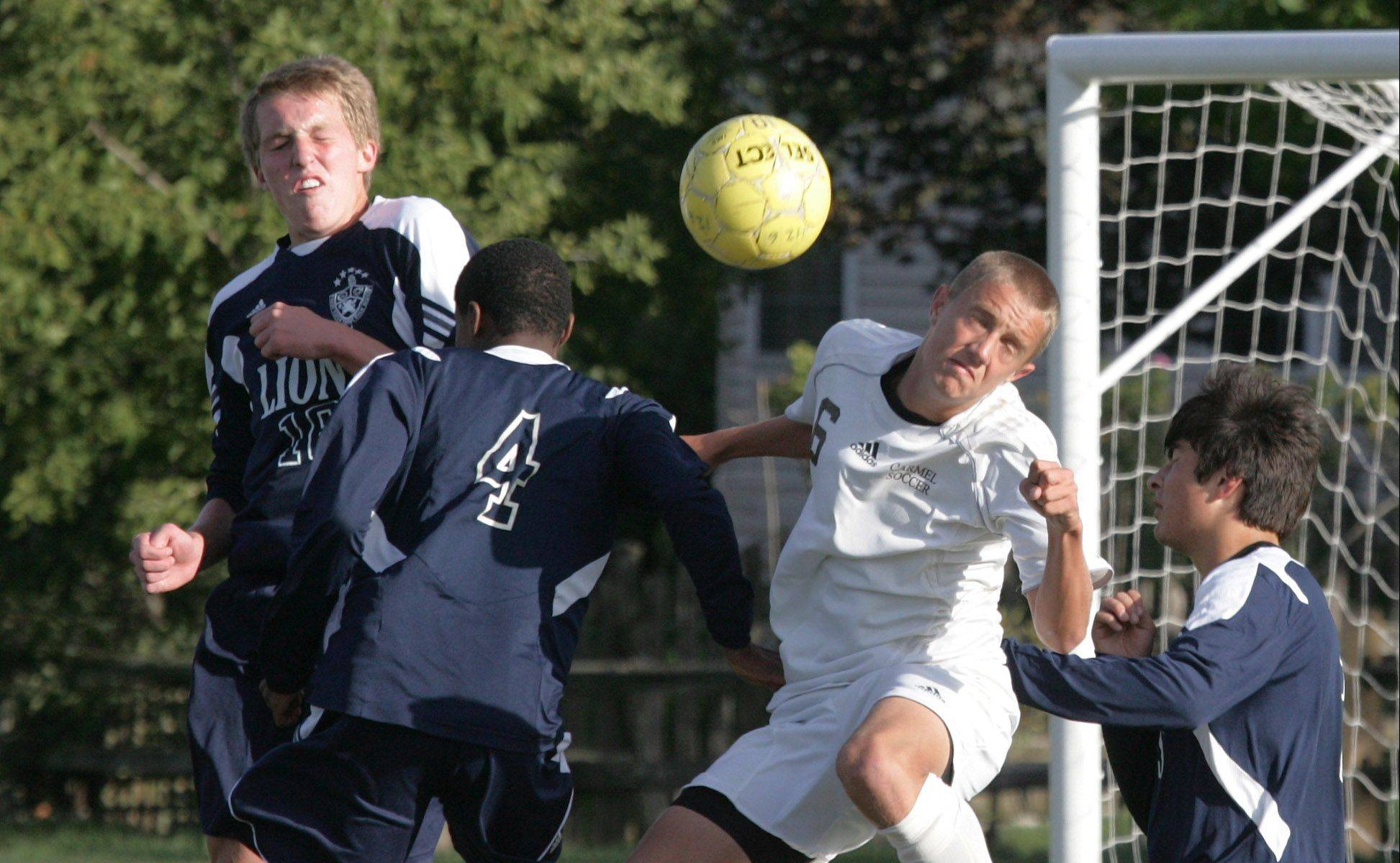 From left, St. Viator's Michel Duszynski and Spencer Moore, Carmel's Evan Potter and St. Viator's Michael Scheer rise up for a header Tuesday in Mundelein.