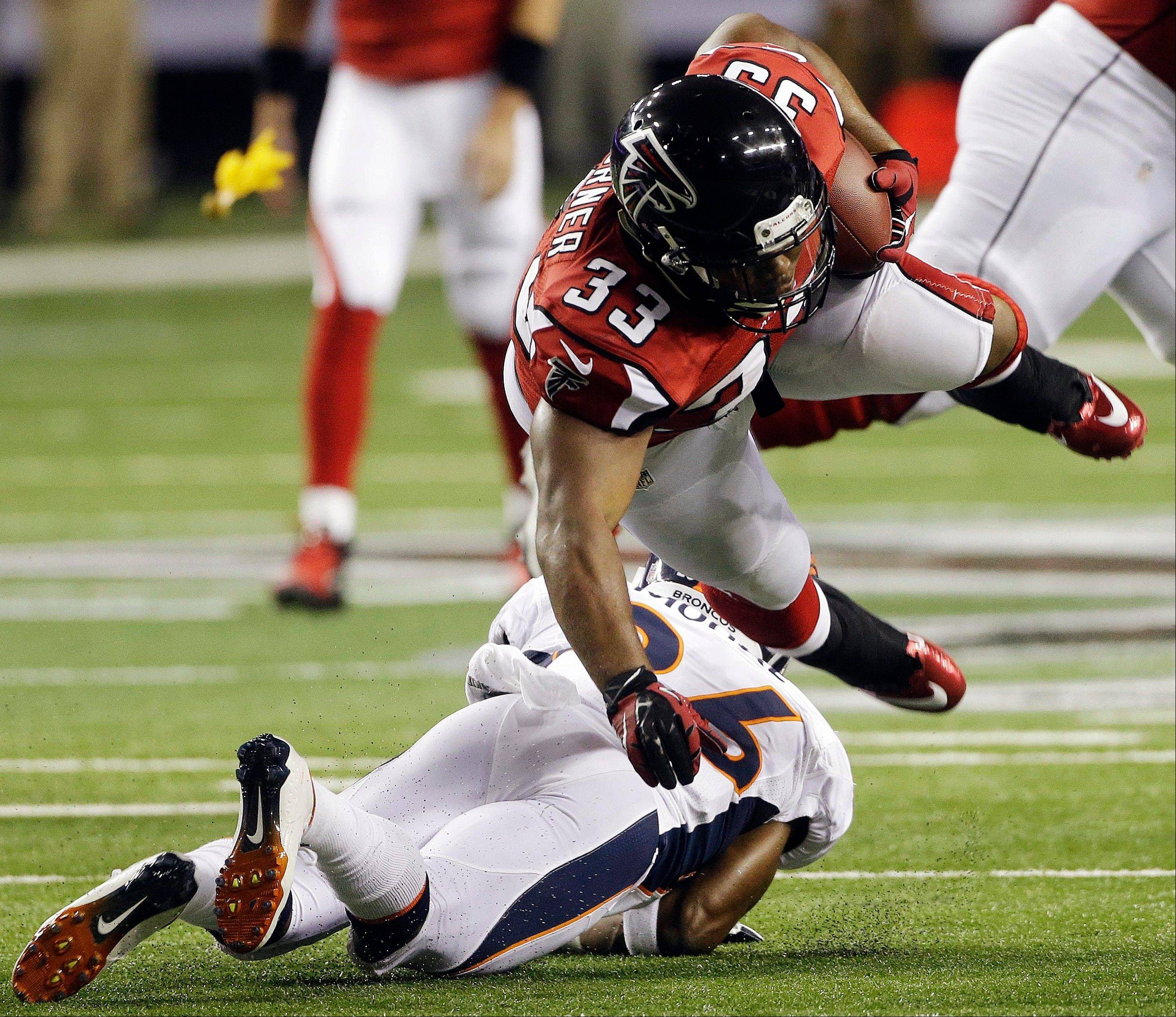 Atlanta Falcons running back Michael Turner (33) is hit by Denver Broncos free safety Rahim Moore (26) in Monday's NFL game. Turner was arrested early Tuesday morning on charges of drunken driving and speeding.