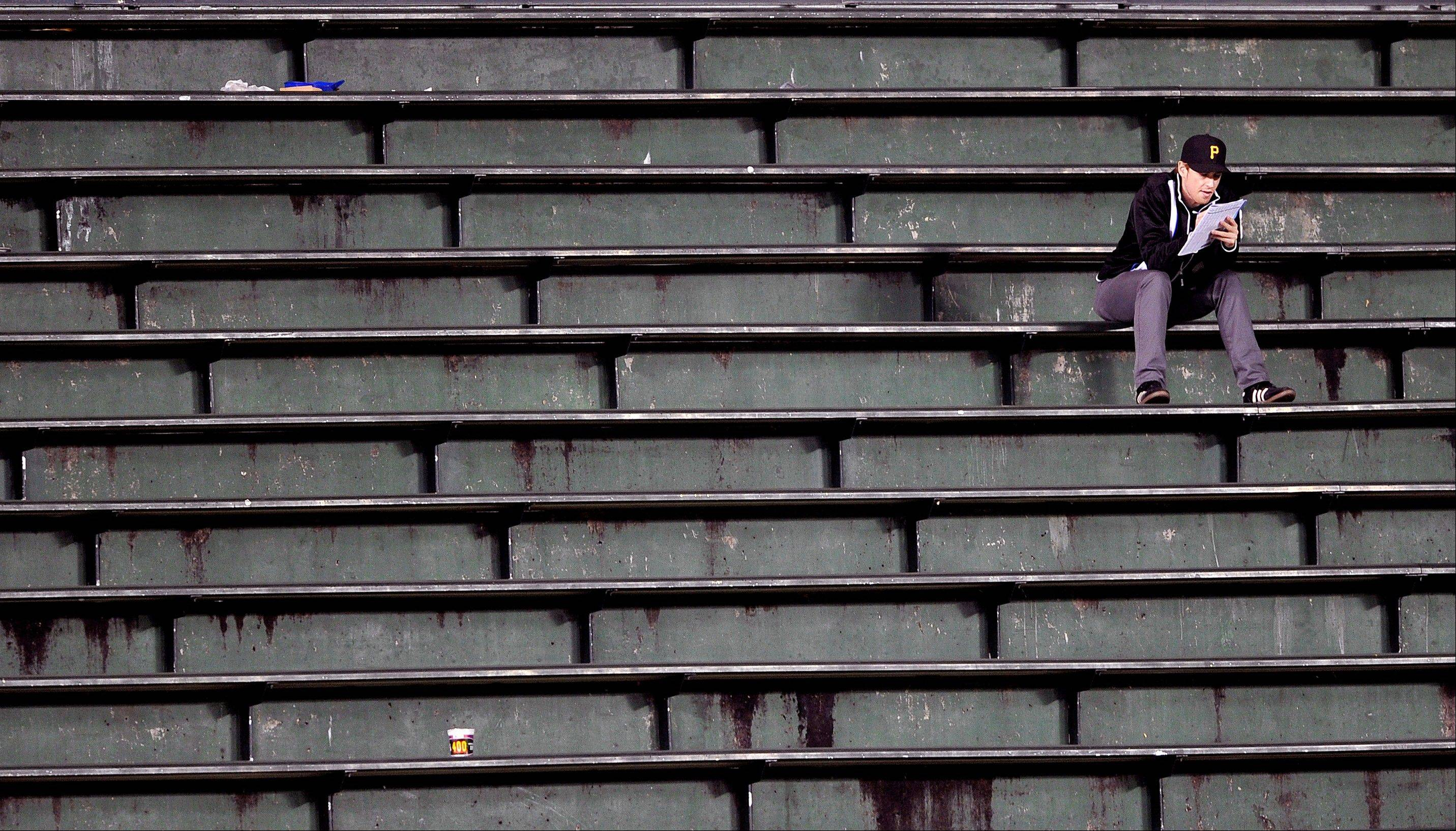 A fan sits all alone in the bleachers during the eighth inning of a baseball game between the Pittsburgh Pirates and Chicago Cubs. It was a Monday night game going into Tuesday morning by then.