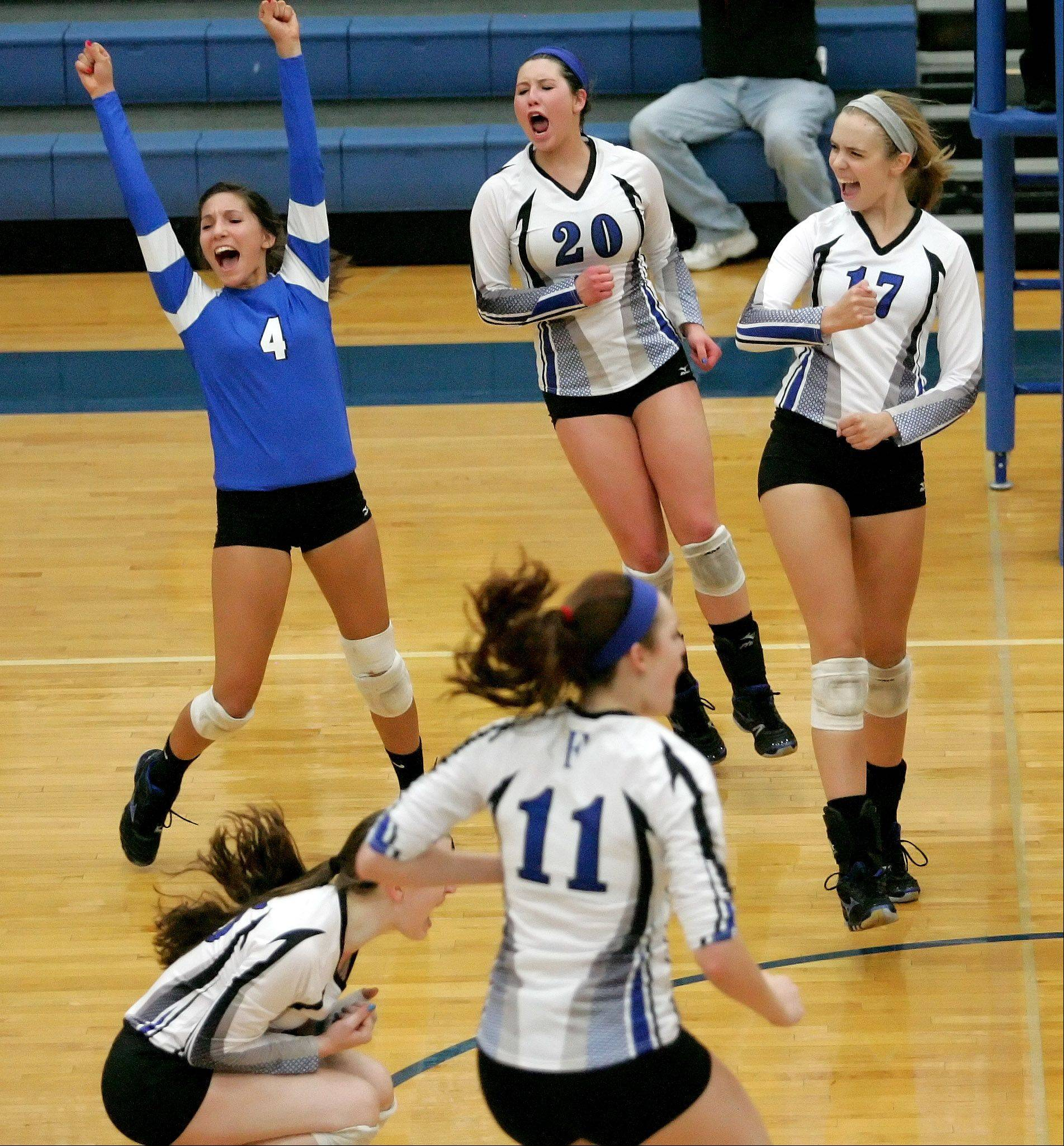 St. Francis players celebrate a point over Rosary during girls volleyball action Monday in Wheaton.