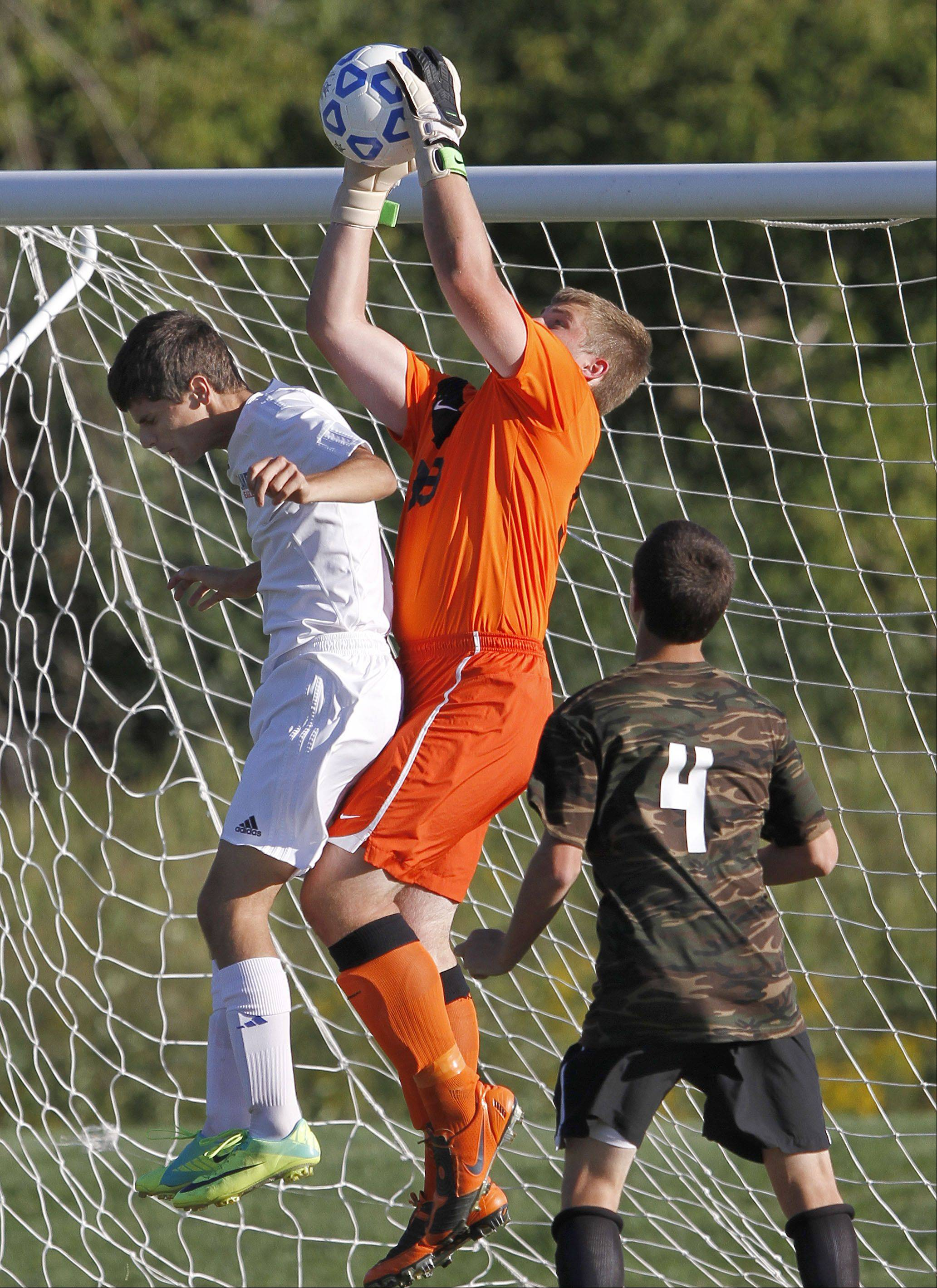 Antioch goalie Tommy Tritschler, middle, goes up for a ball with Lakes' Joey Savino as Antioch's Thomas Furlong looks on during their game Tuesday in Lake Villa.