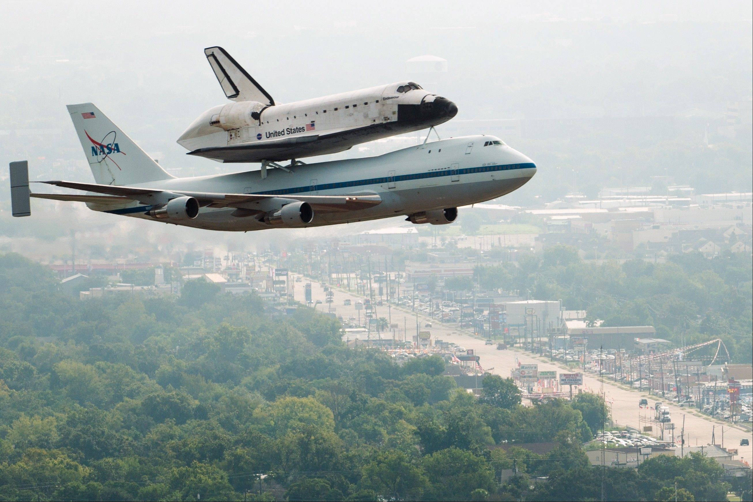 The space shuttle Endeavour, carried atop NASA's 747 Shuttle Carrier Aircraft, passes over neighborhoods near Hobby Airport during a flyover on Wednesday in Houston. Endeavour stopped in Houston on its way from the Kennedy Space Center to the California Science Center in Los Angeles, where it will be placed on permanent display.