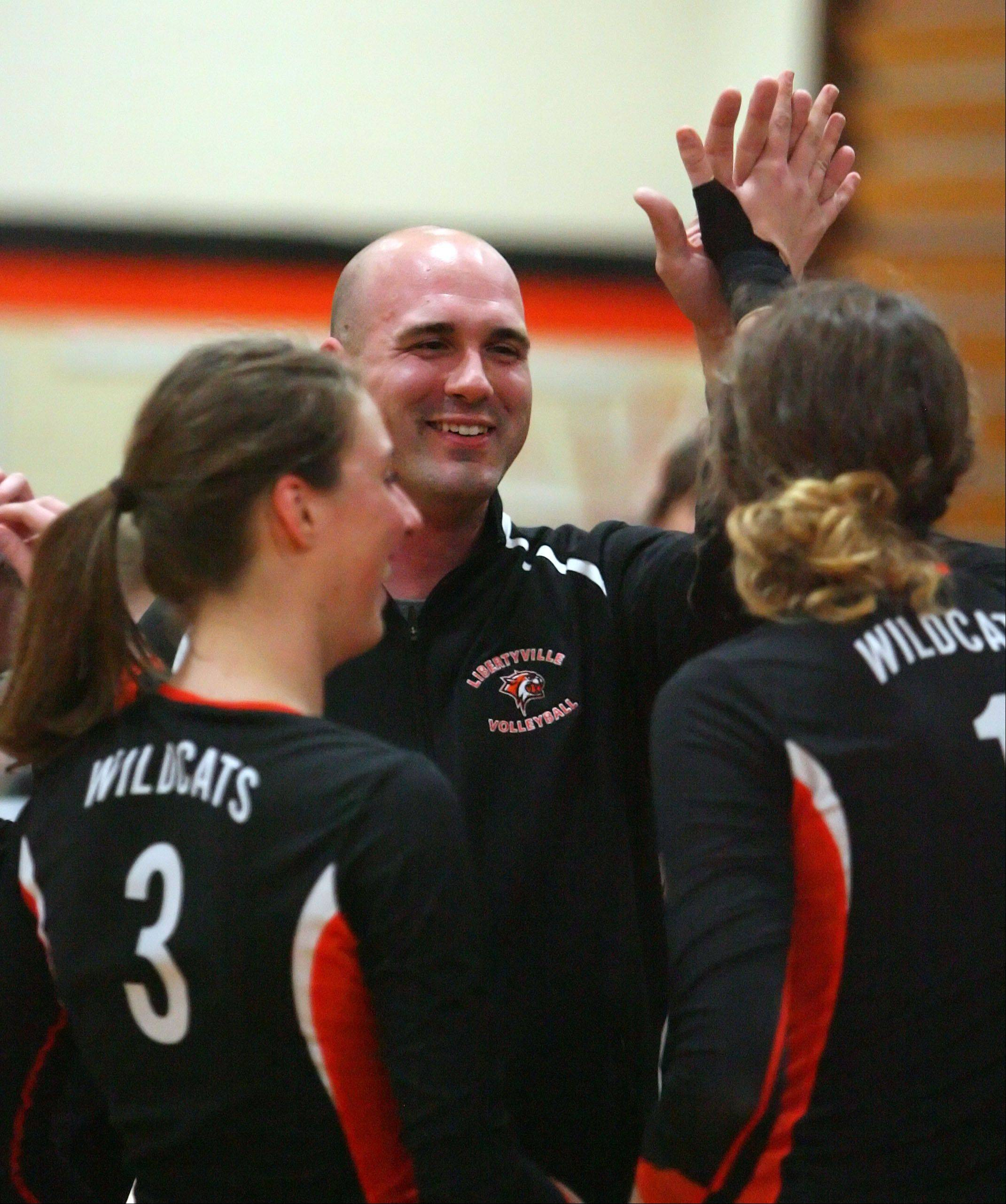 Libertyville coach Greg Loika celebrates his 100th win with his players after the Wildcats defeated Stevenson Wednesday night at Libertyville.