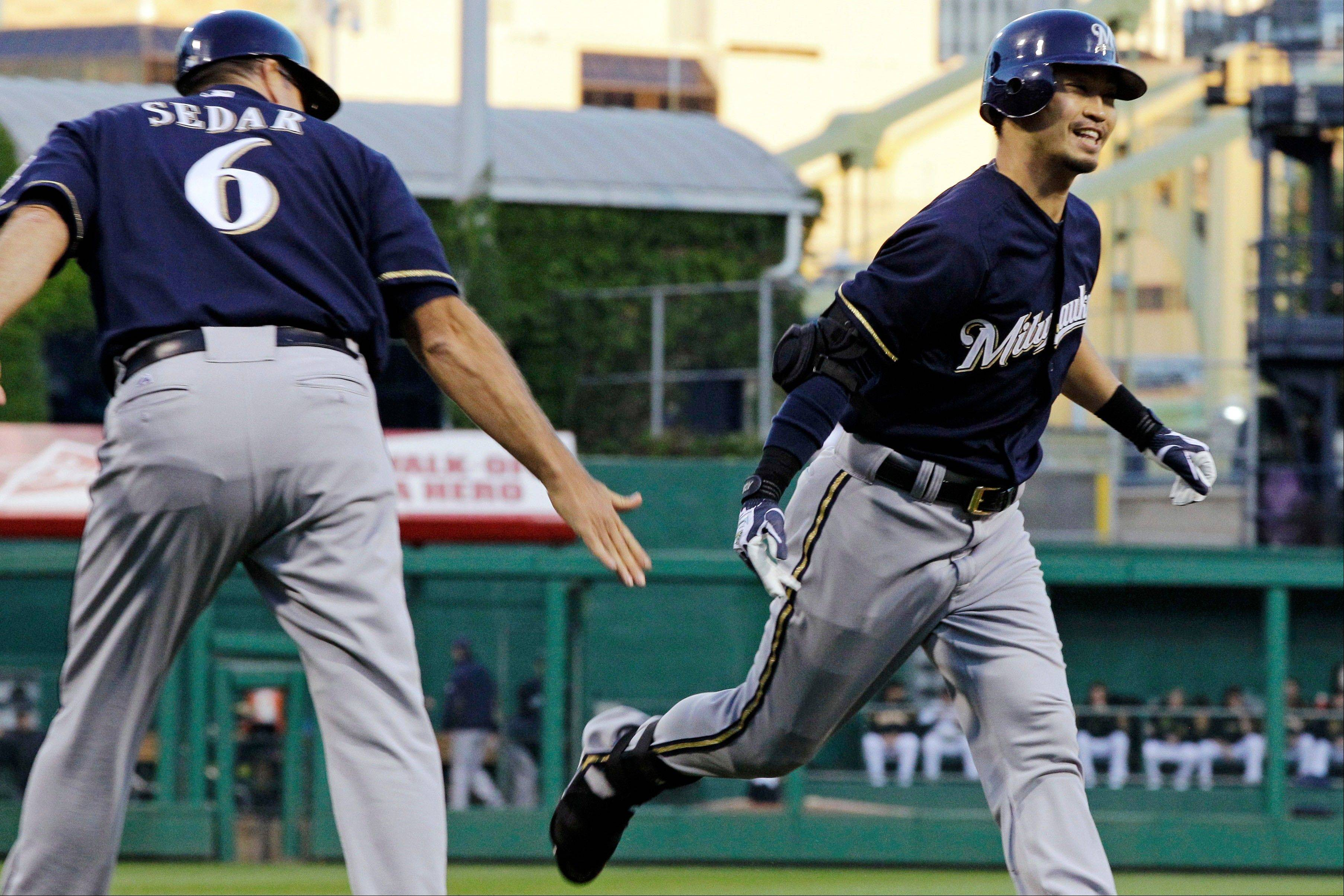 The Milwaukee Brewers' Norichika Aoki is congratulated Wednesday by third base coach Ed Sedar after hitting a solo home run off Pittsburgh Pirates starting pitcher Kyle McPherson during the first inning in Pittsburgh.