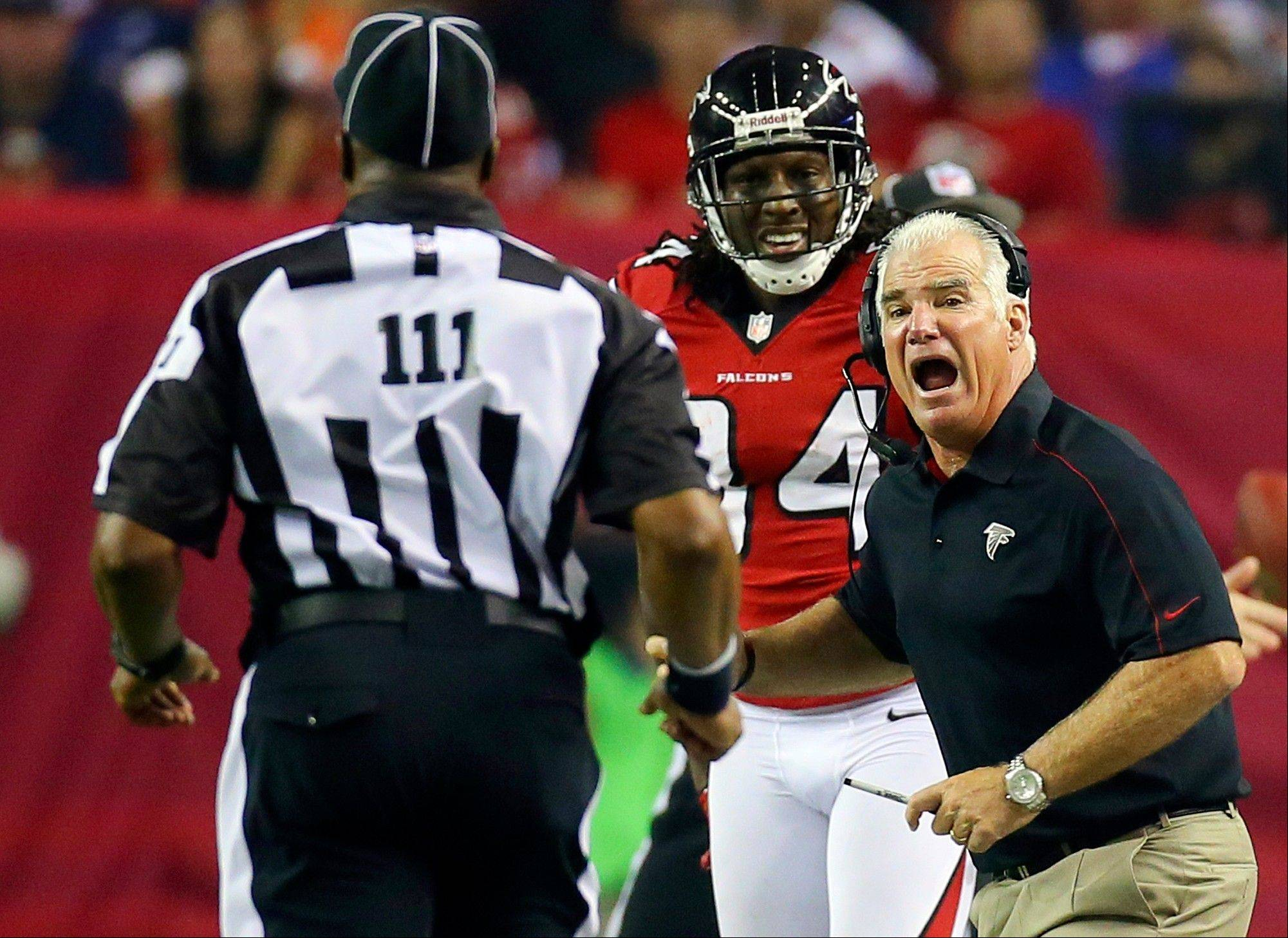 Atlanta Falcons head coach Mike Smith, right, argues for a pass interference call on a play involving wide receiver Roddy White, center, with an official Monday. Statistics show strong similarities between this year's number of penalties and last year's flags thrown by the guys who are currently locked out.