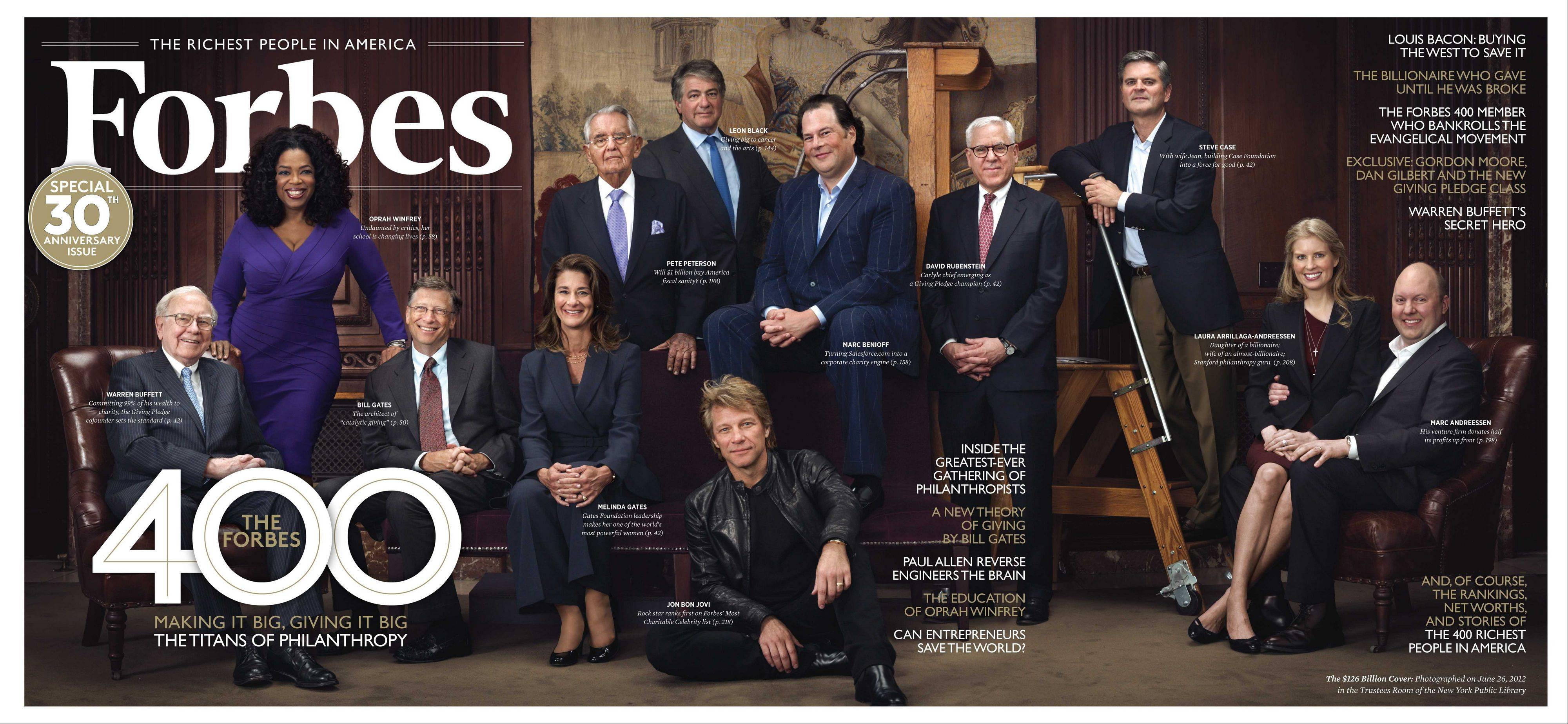 From left to right: Warren Buffett, Oprah Winfrey, Bill Gates, Melinda Gates, Pete Petersen, Leon Black, Jon Bon Jovi (seated on the ground), Marc Benioff, David Rubenstein, Steve Case, Laura Arrillaga-Andreessen, Marc Andreessen posing for a portrait in the Trustees Room at the New York Public Library in New York.