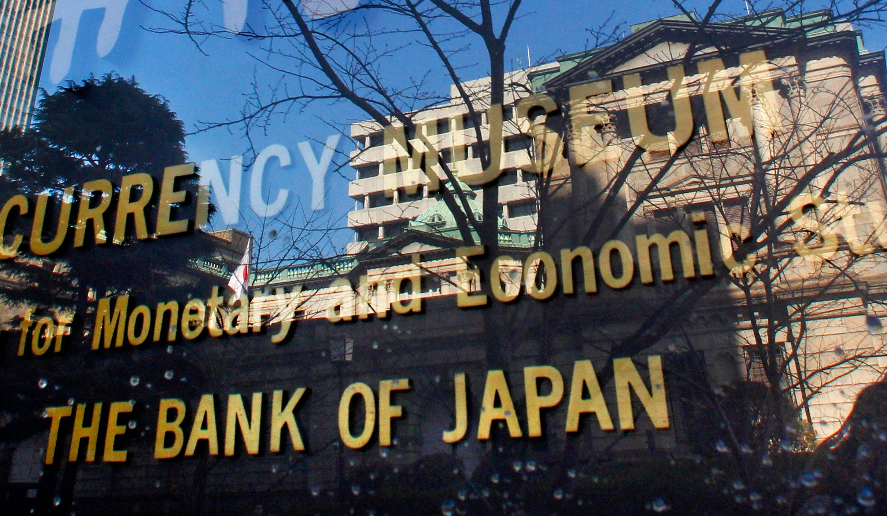 The Bank of Japan building is reflected on the glass covering the plate of its adjunct museum in Tokyo. Japan's central bank expanded its monetary easing by 10 trillion yen ($126 billion) Wednesday.