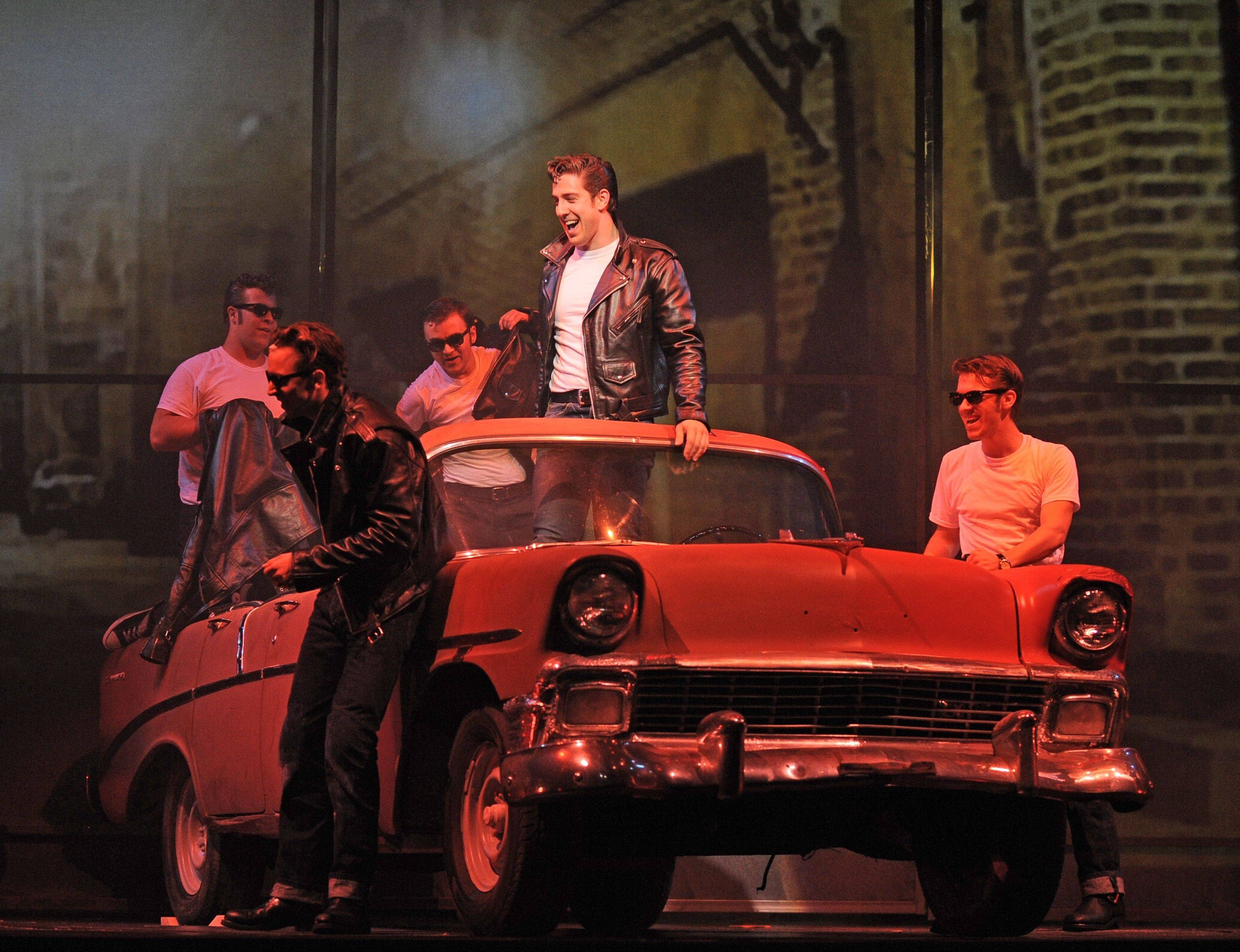 "Kenickie (Adrian Aguilar, center in car) extols the future virtues of ""Greased Lightnin'"" in ""Grease"" at the Paramount Theatre in Aurora."
