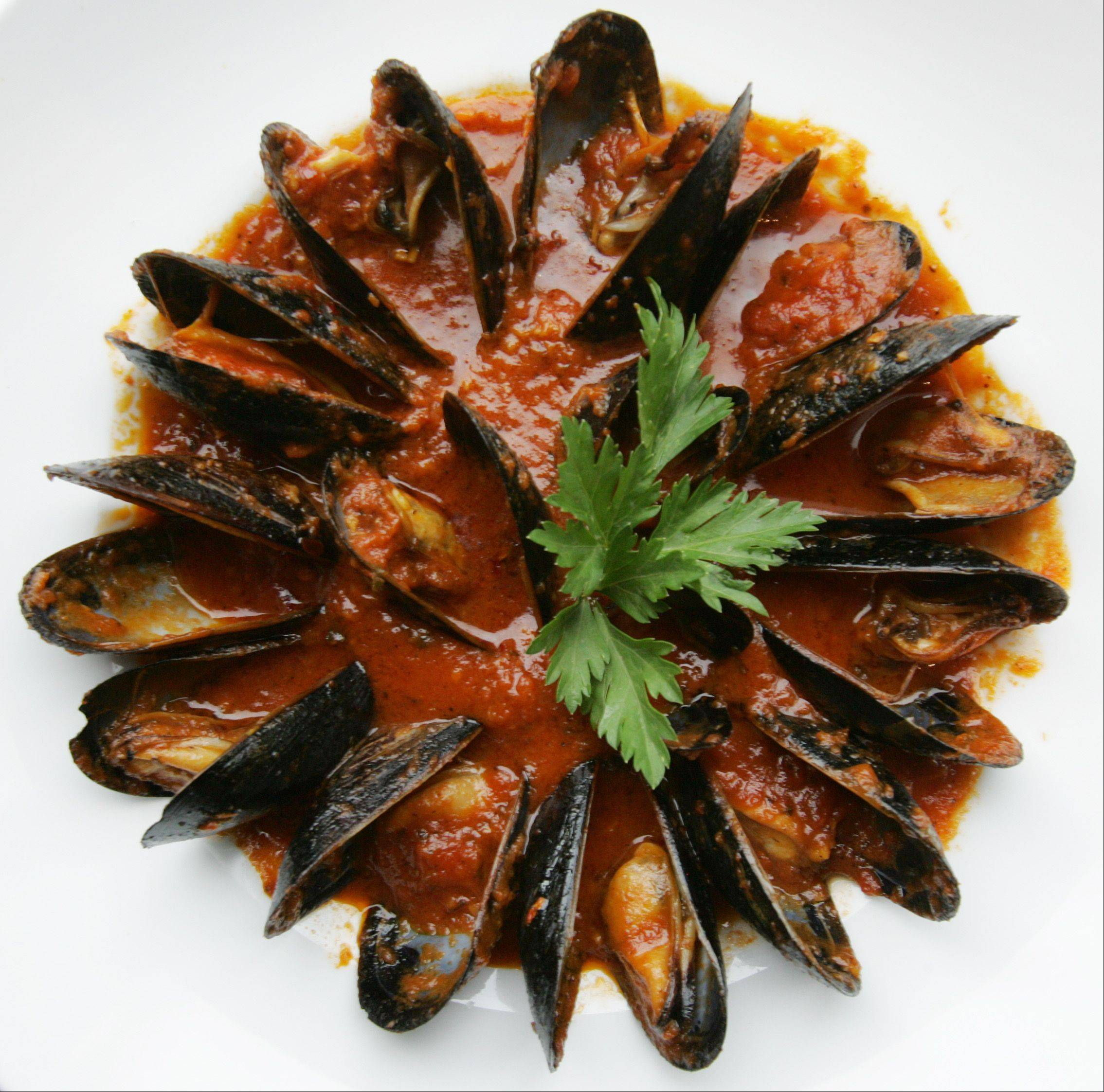 Mussels in white wine tomato sauce with pancetta and shallots are a popular way to start a meal at Marzano's Wood Fired Italian restaurant in McHenry.