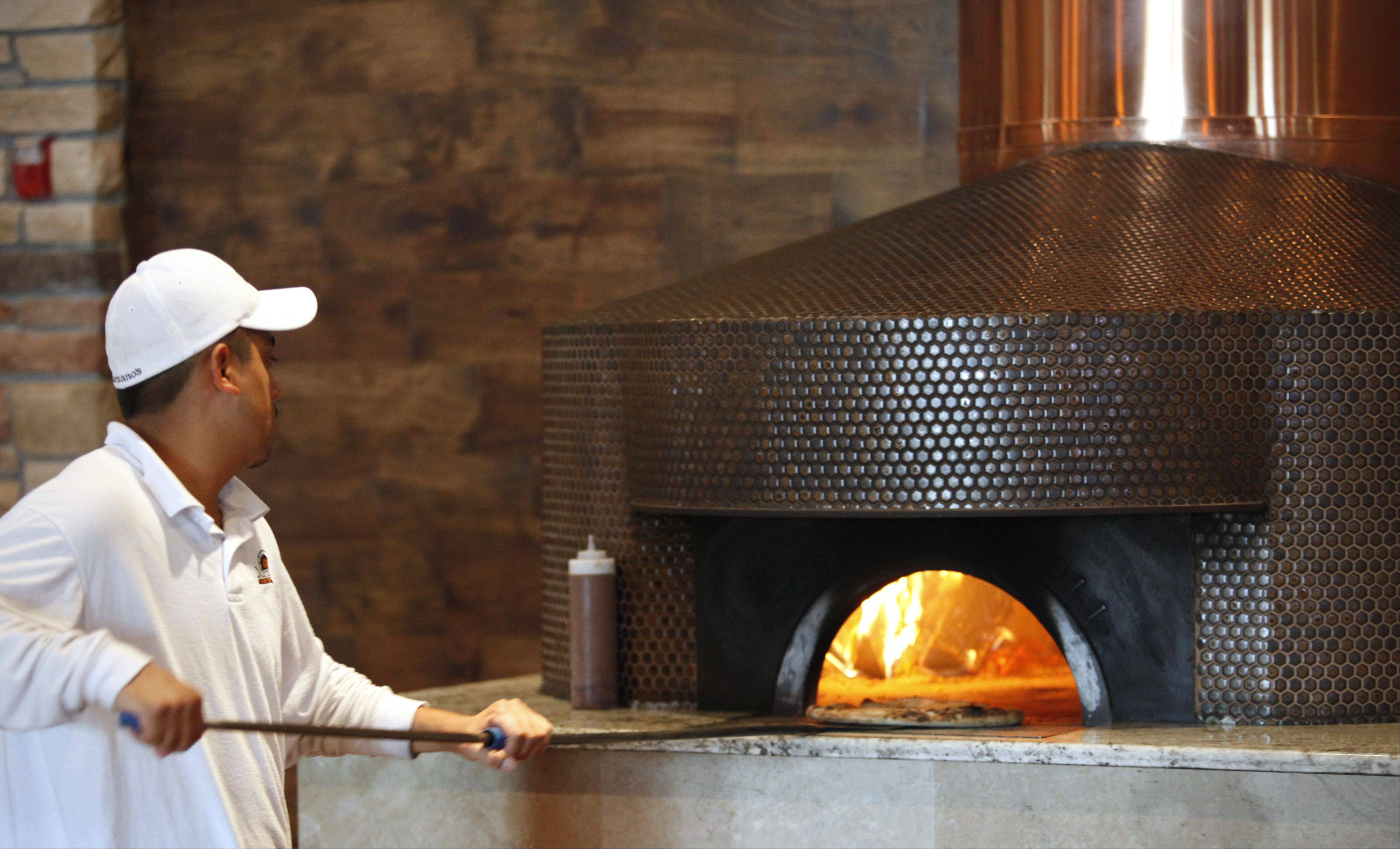 A pizza heads into the wood-fired oven at Marzano's Wood Fired Italian restaurant.