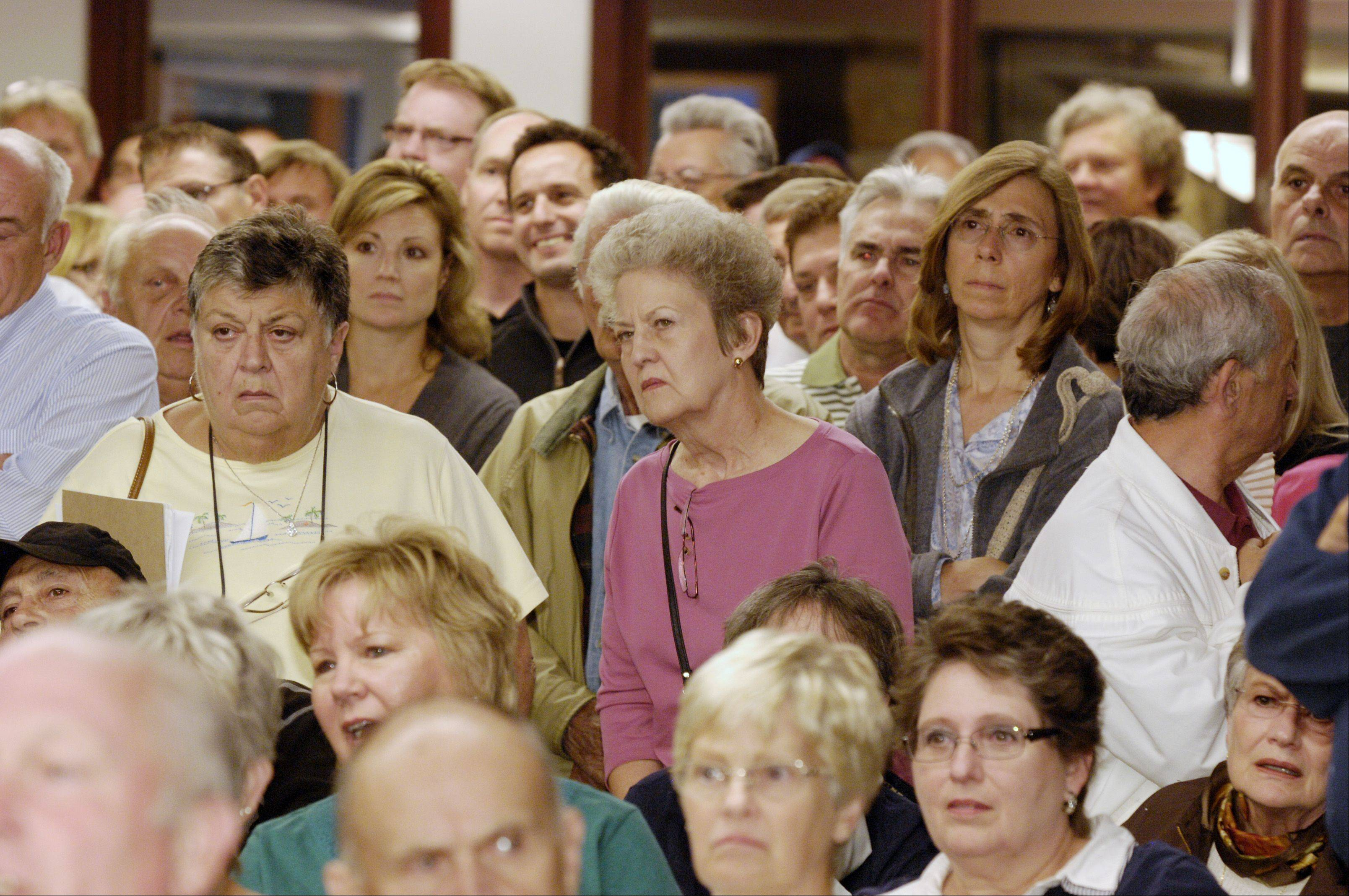 Disapproving Itasca residents listen Wednesday as Itasca plan commission Chairman Mark Kischner postponed a public hearing on a proposed church. The fire marshal estimated 400 people were there, well beyond the 267-person occupancy for the village hall board room. The new hearing will be at 7 p.m. Oct. 17.