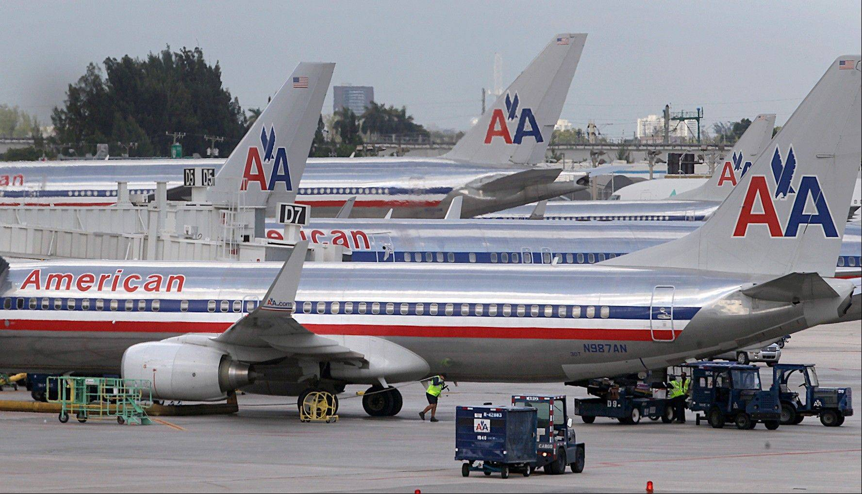 American Airlines jets are parked at the various gates of Miami International Airport on Tuesday. In addition to sending layoff warning notices to more than 11,000 employees this week, the airline has canceled hundreds of flights this week because of pilot absences.