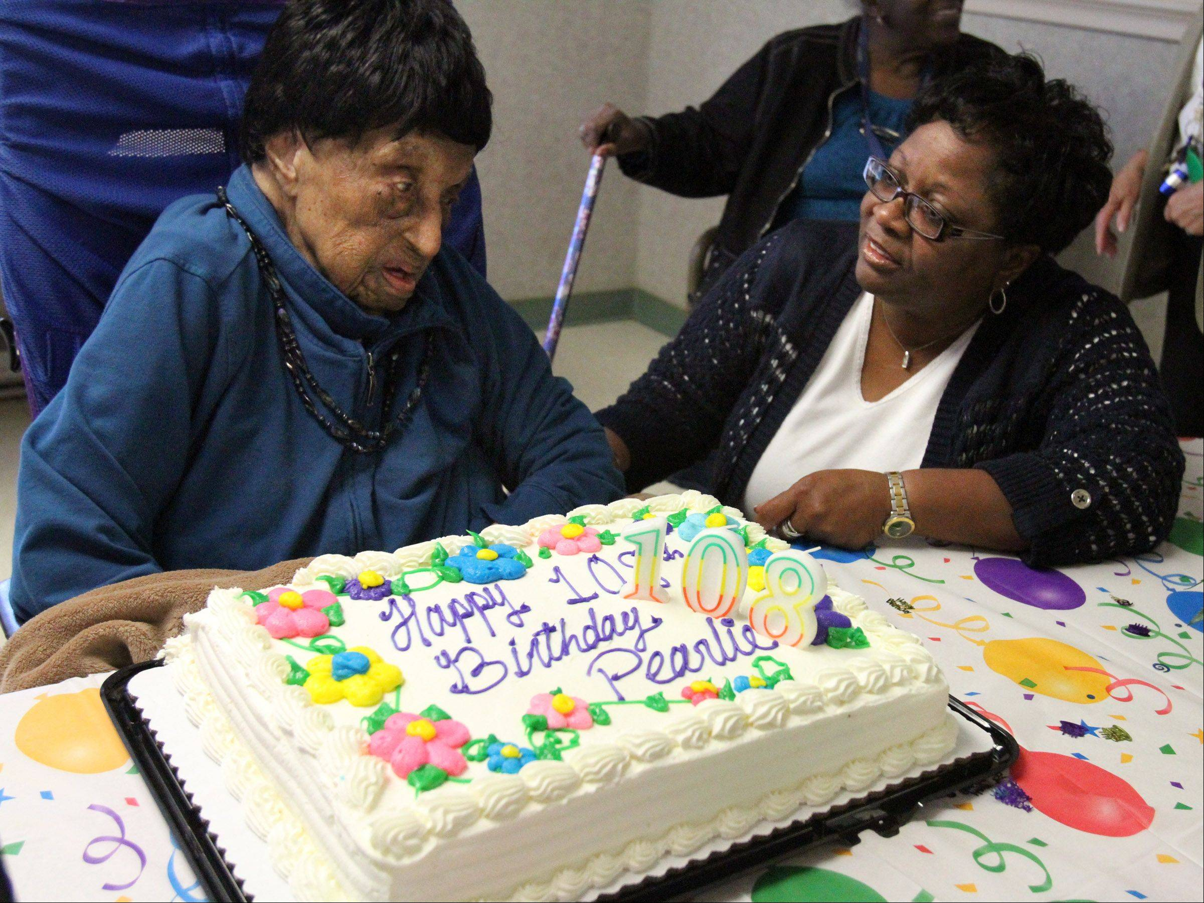 Alma Booker of Round Lake Beach helps her grandmother, Pearlie Young, celebrate her 108th birthday with a cake and candles at Hillcrest Nursing Center in Round Lake Beach on Wednesday.