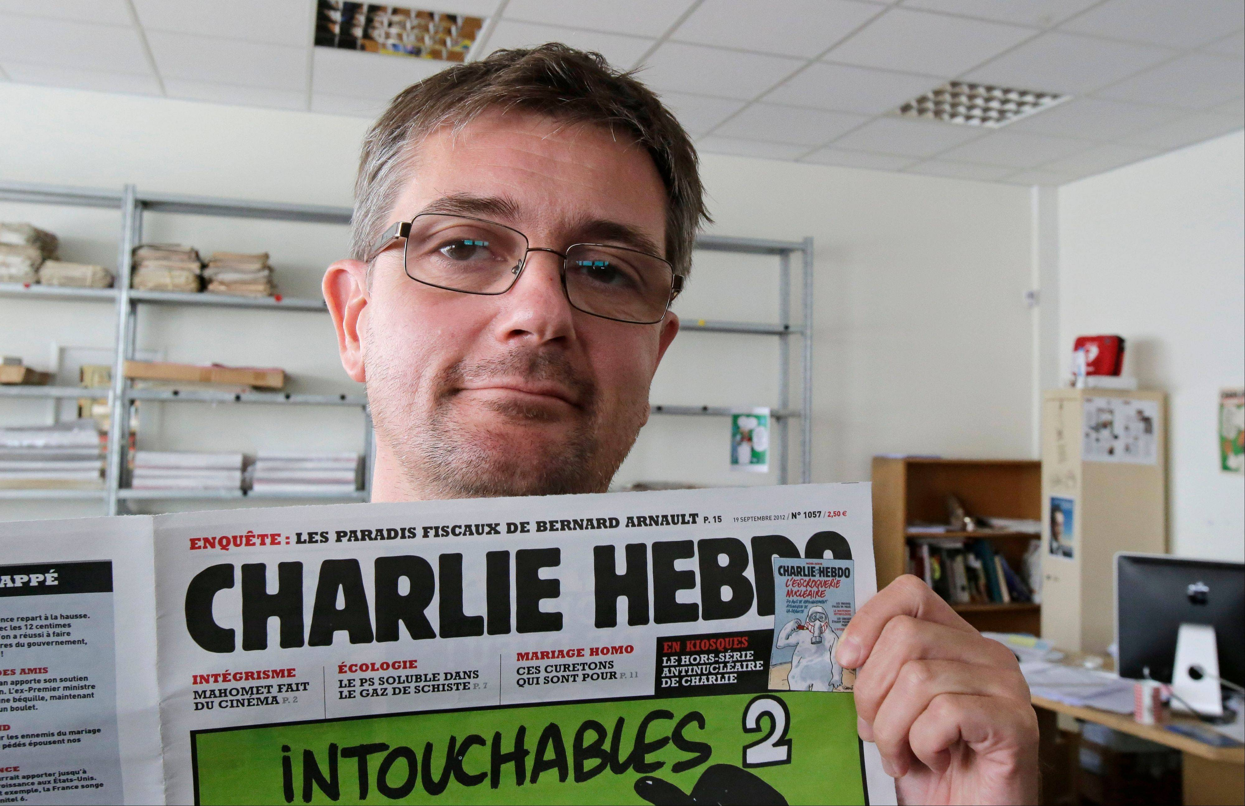 Charb, the publishing director of the satyric weekly Charlie Hebdo, displays the front page of the newspaper in Paris Wednesday. Police took up positions outside the office after it published crude caricatures of the Prophet Muhammad.