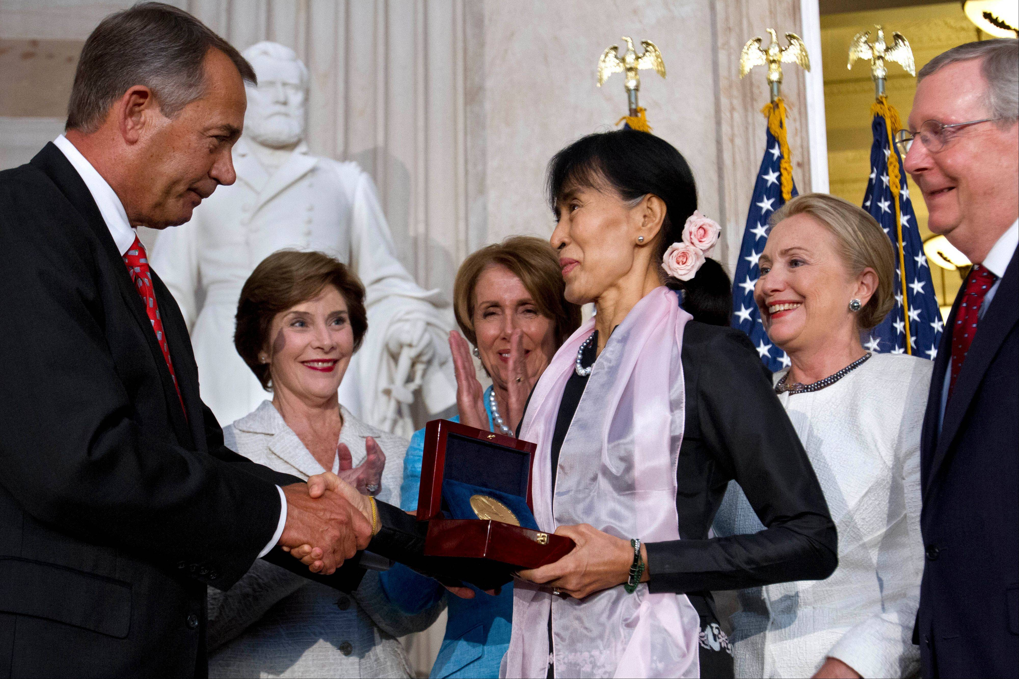 Myanmar democracy leader Aung San Suu Kyi, center, receives the Congressional Gold Medal from Speaker of the House John Boehner, at the U.S. Capitol Wednesday, as former first lady Laura Bush, back left, House Democratic Leader Nancy Pelosi, Secretary of State Hillary Rodham Clinton and Senate Republican Leader Mitch McConnell watch.