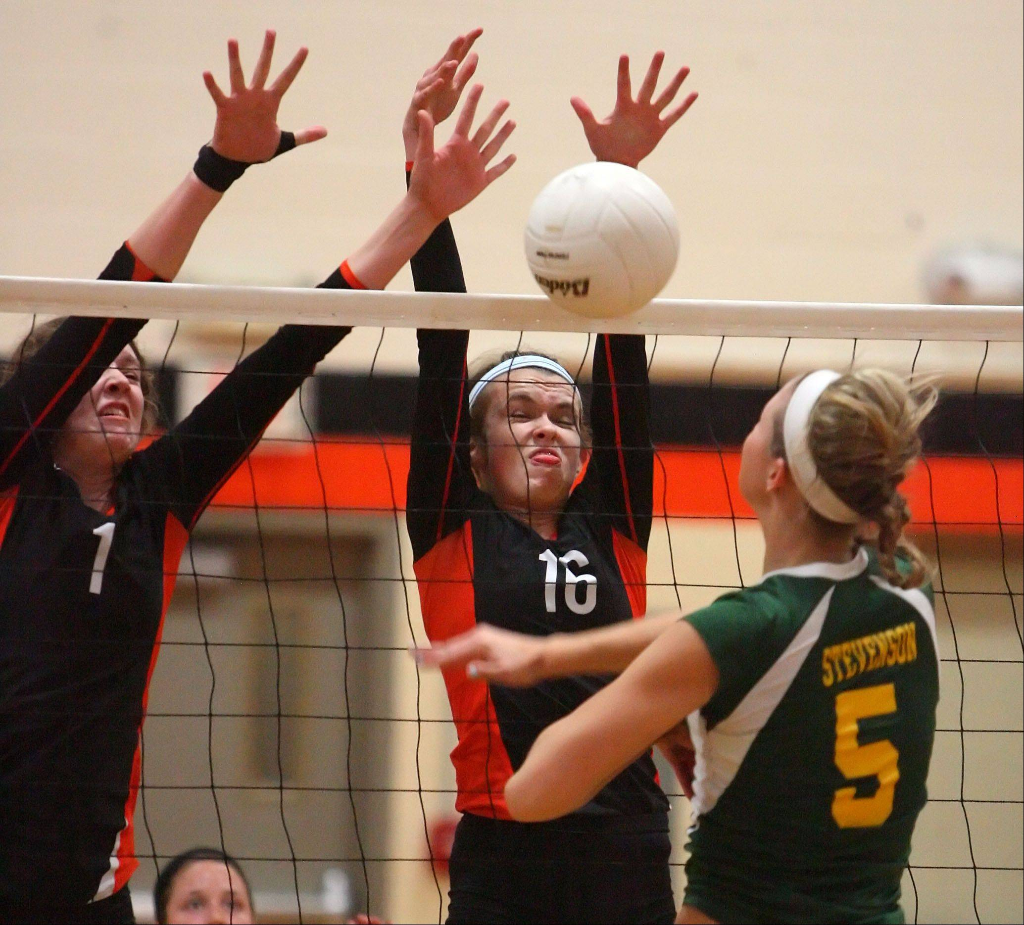 Libertyville's Alex Basler, left, and Rhiannon Prentiss block the attack by Stevenson's Jenna Radtke during the Wildcats' 3-set win Wednesday night at Libertyville.