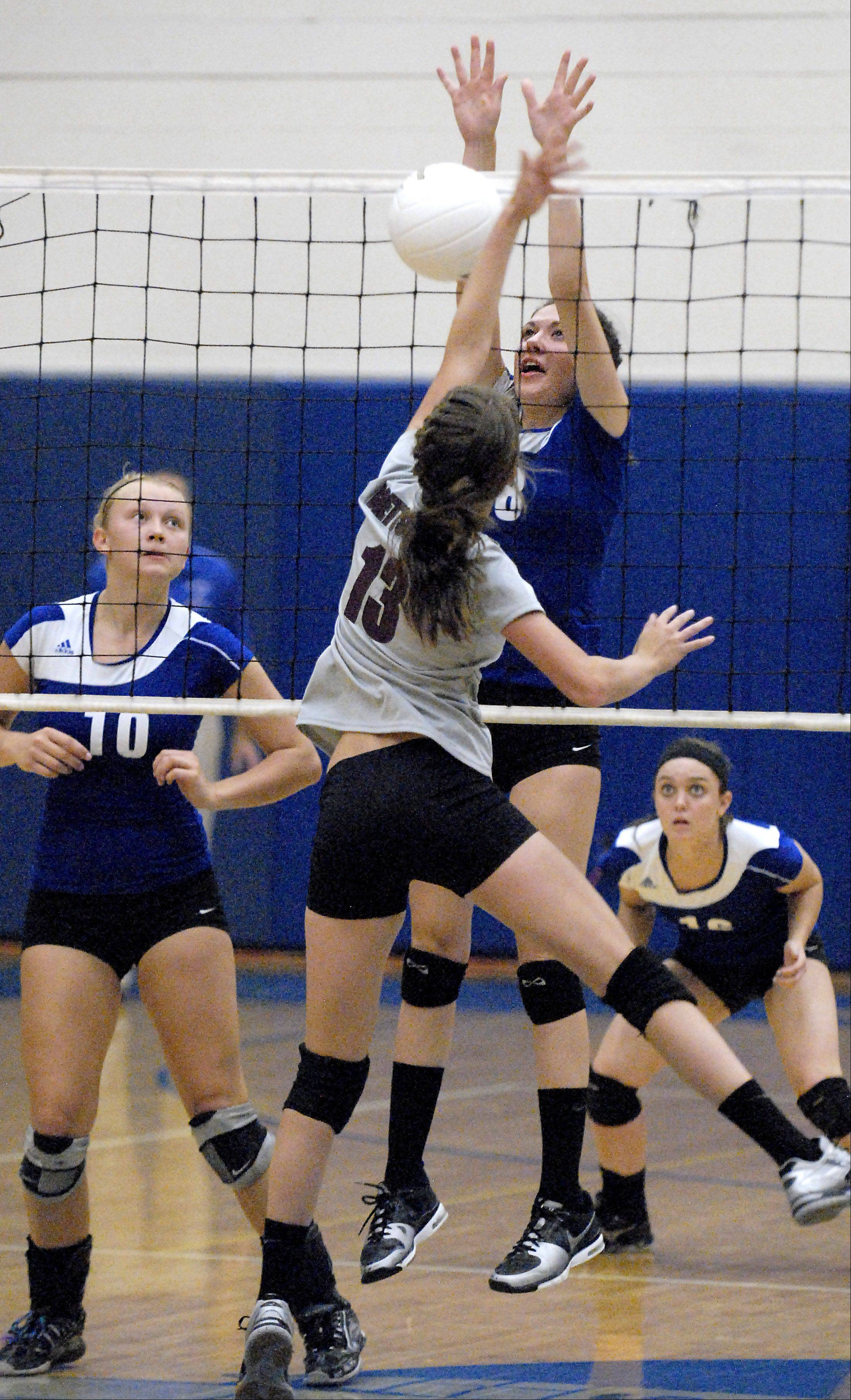 Burlington Central's Lauren Peltonen block a spike by Marengo's Logan Brettschneider in the second set on Wednesday at Burlington Central.