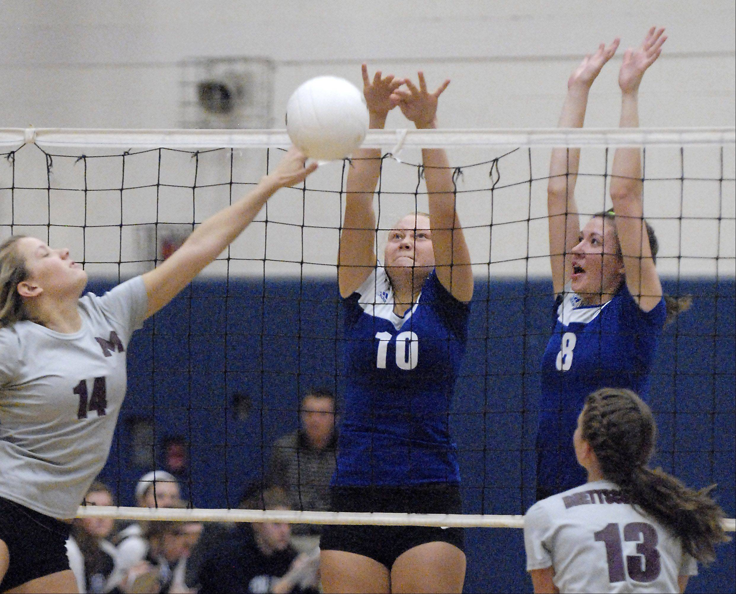 Burlington Central's Jess Emrich and Lauren Peltonen immediately deflect a shot to sending Marengo's Peyton Velasquez to scramble in the second set on Wednesday.