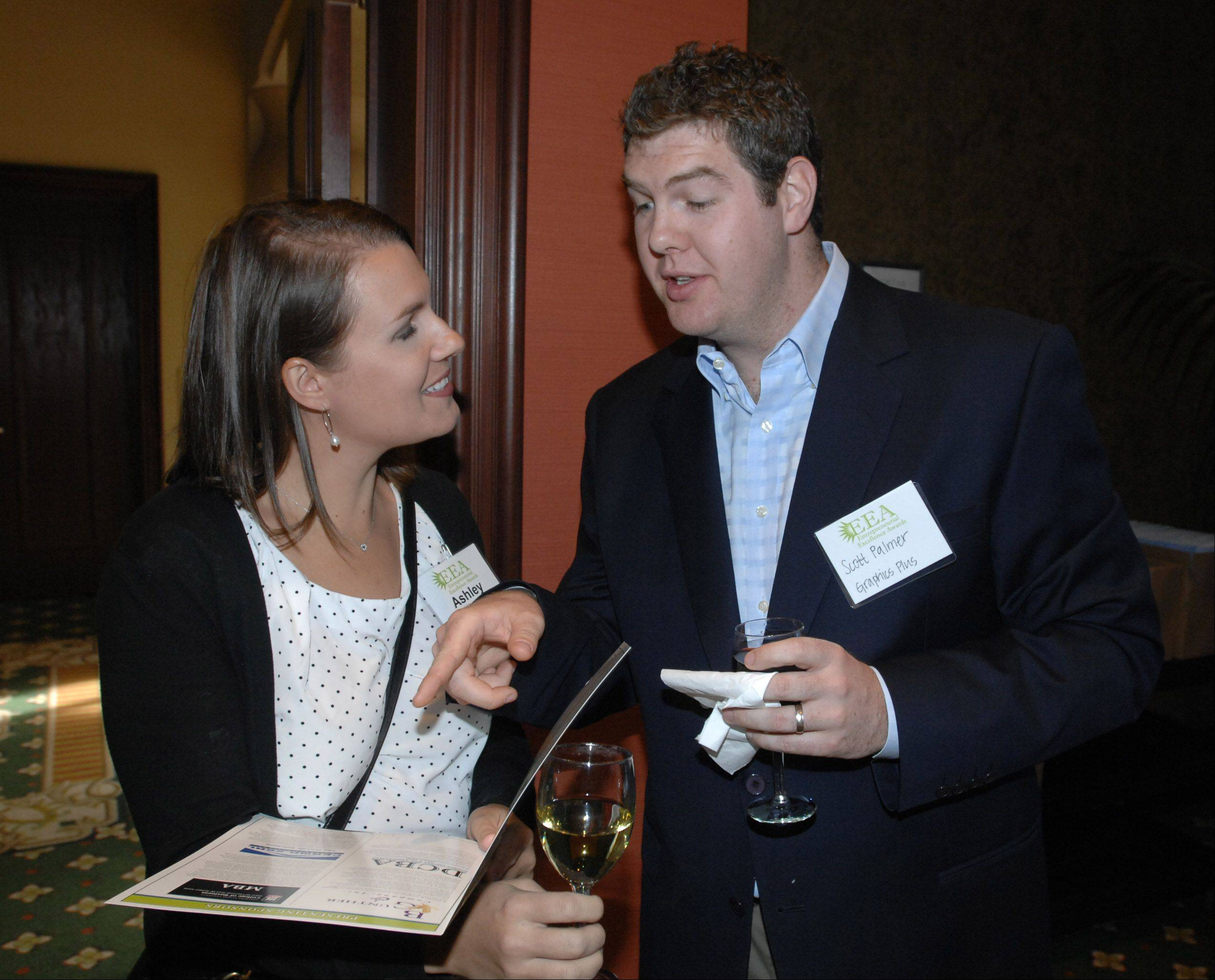 Ashley and Scott Palmer of Graphics Plus in Lisle look over the program at the 13th Annual Entrepreneurial Excellence Awards at Medinah Banquets in Addison Thursday.