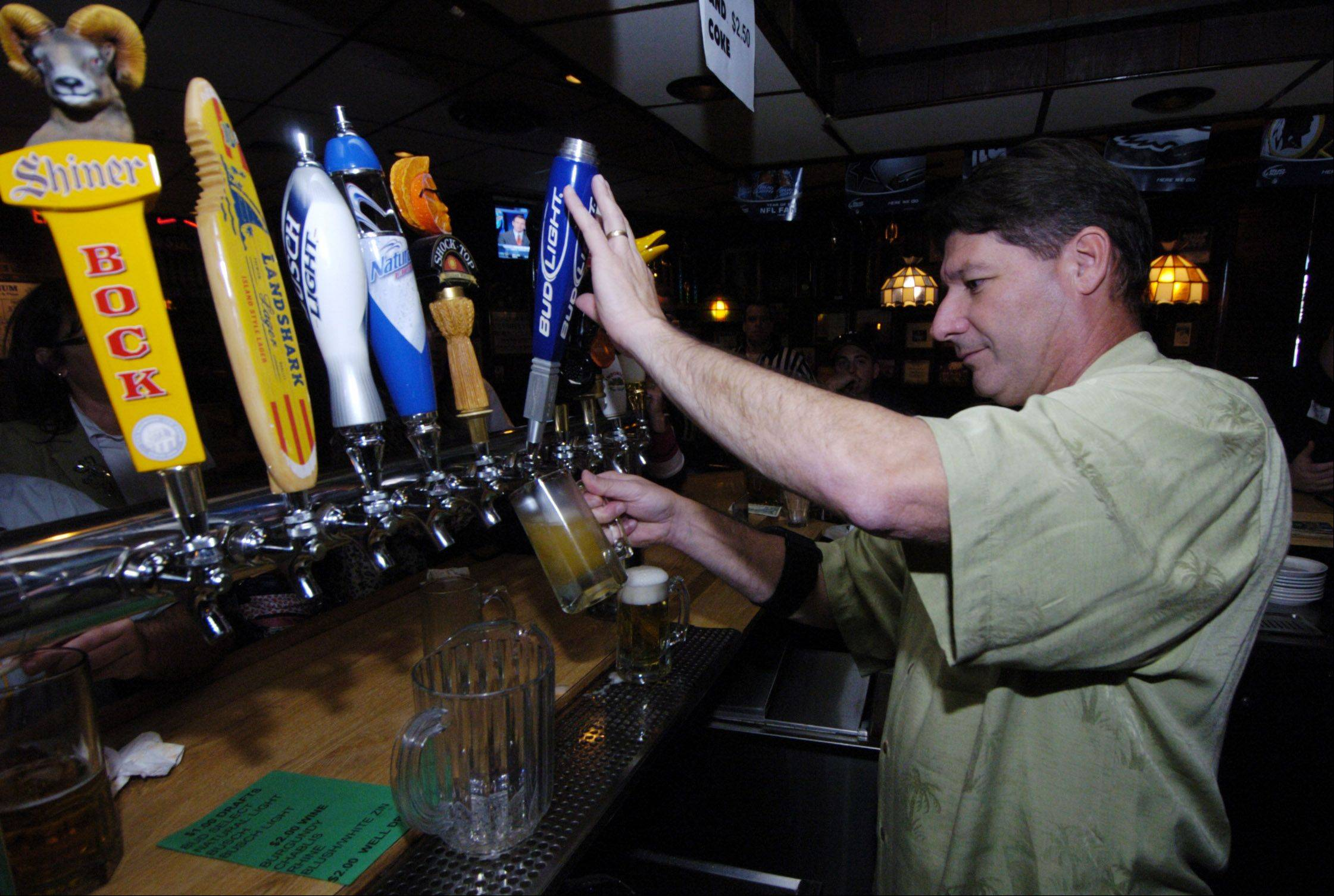 Jeff Palombo, senior vice president and general manager of Northrop Grumman, pours a beer Thursday as he competes as a celebrity bartender at Stadium Sports Club for the Rolling Meadows Chamber of Commerce.