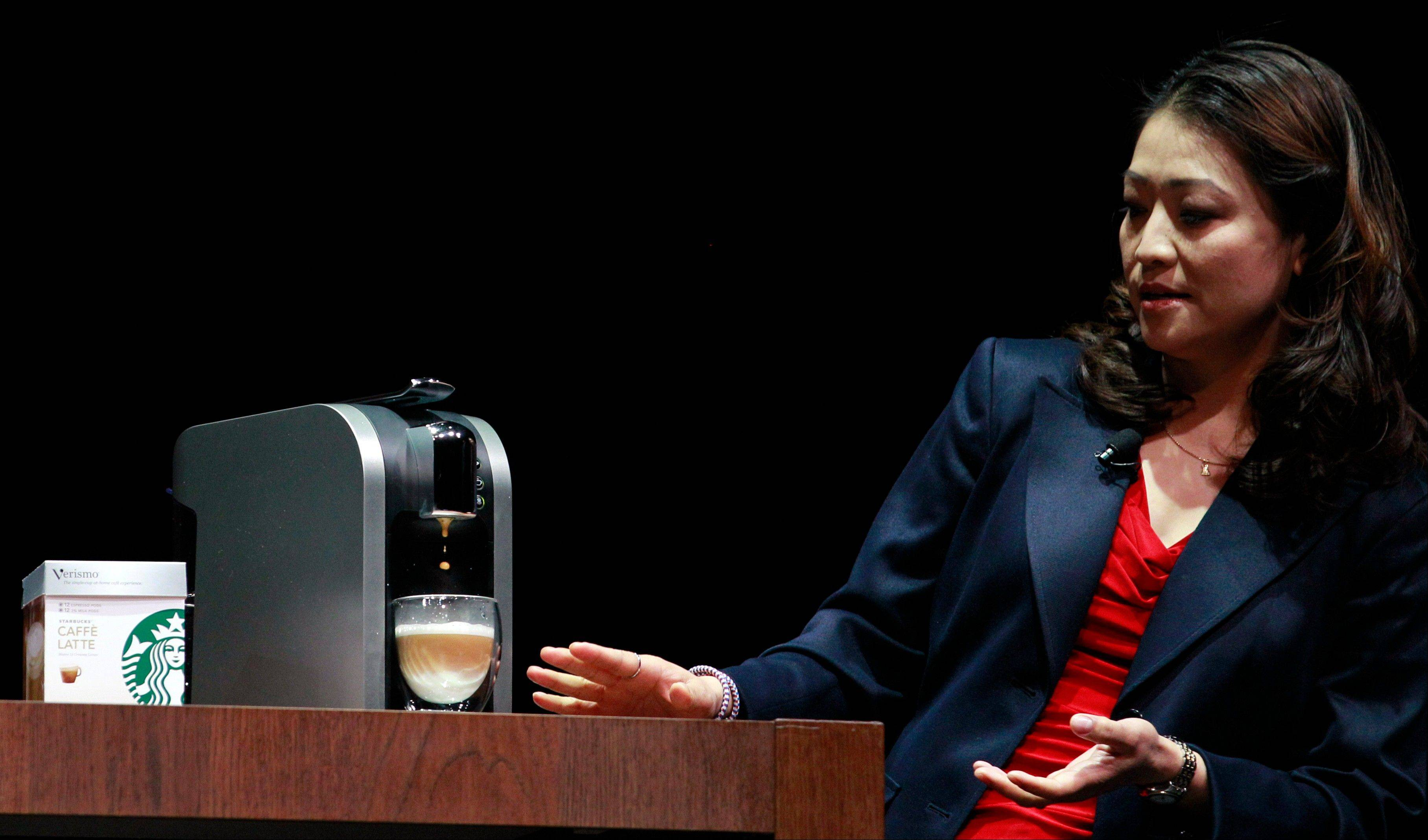 "Hannah So demonstrates a ""Verismo,"" a single-serving espresso machine, at the annual Starbucks shareholders meeting."