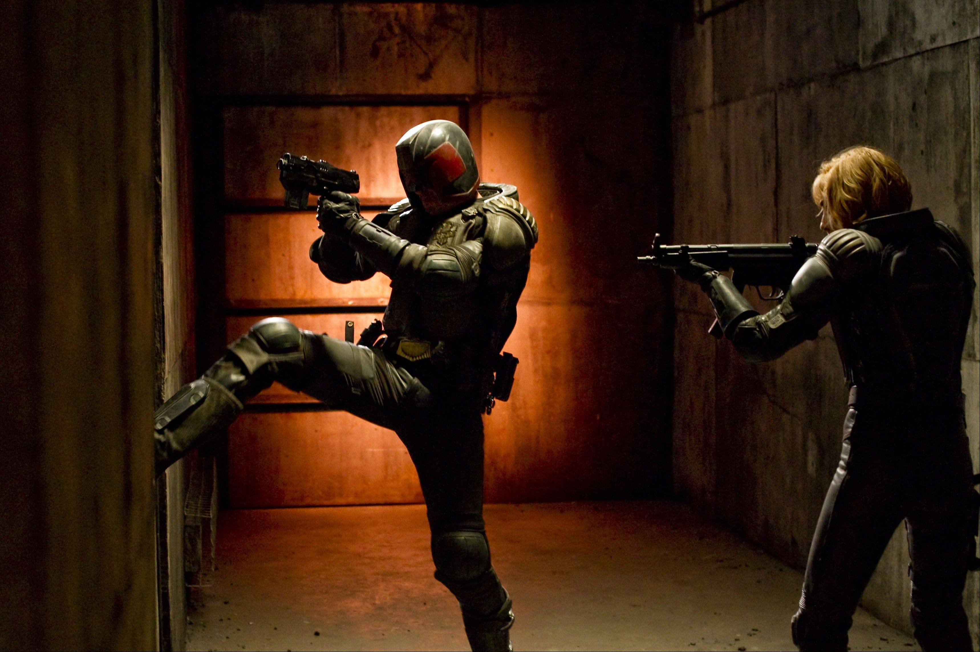 "Judge Dredd (Karl Urban) kicks down a door with help from his psychic assistant (Olivia Thirlby) in the science-fiction action thriller ""Dredd 3-D."""