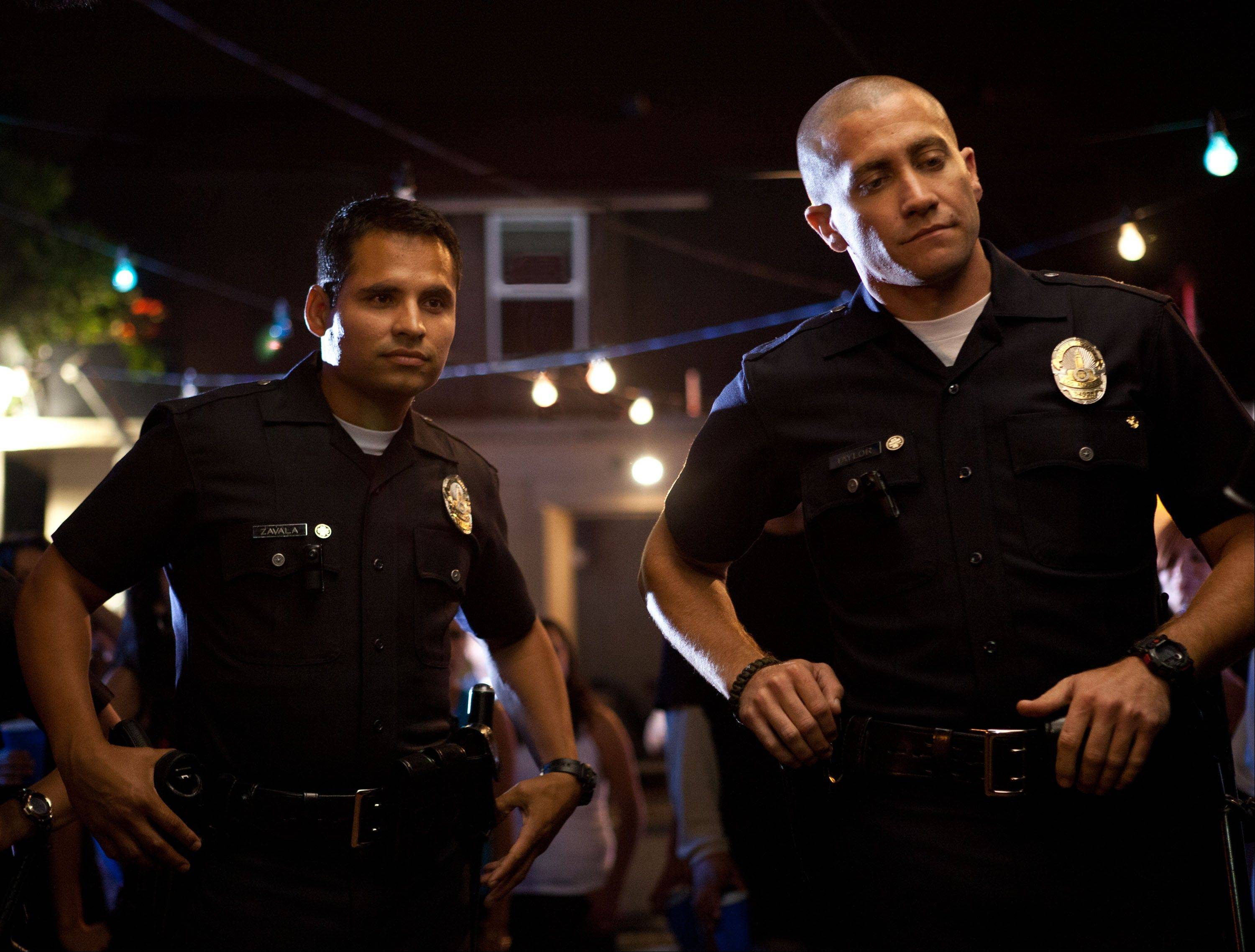 "Police officers Mike Zavala (Chicago's Michael Pena), left, and Brian Taylor (Jake Gyllenhaal) go about protecting Los Angeles in the found footage production of ""End of Watch."""