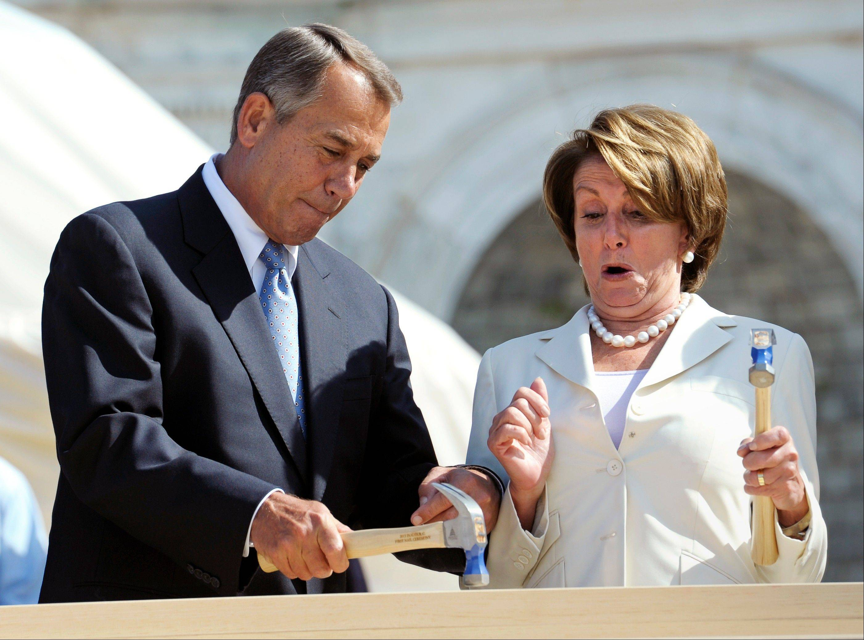 Speaker of the House John Boehner finishes hammering a nail into a plank with House Democratic Leader Nancy Pelosi during the First Nail Ceremony for the official launch of construction of the inaugural platform, where the president will take the oath of office in January.