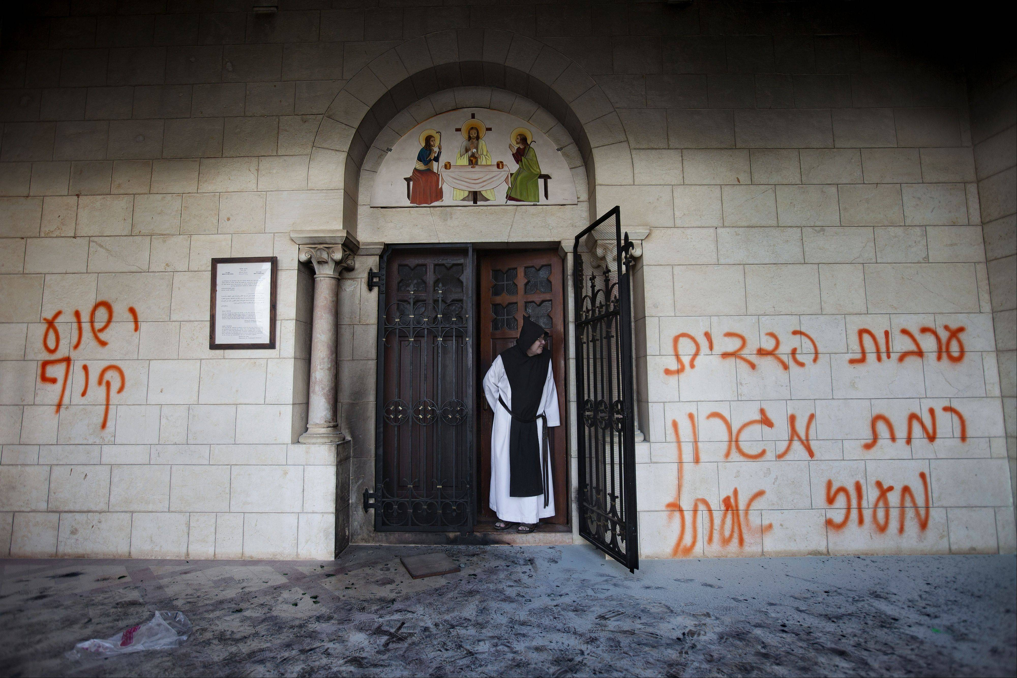 "A Catholic monk stands in a doorway of the Latrun Trappist Monastery where Israeli police say vandals spray-painted anti-Christian and pro-settler graffiti and set the monastery's door on fire, in Latrun, between Jerusalem and Tel Aviv, Israel. After a series of attacks on Christian holy sites in Israel, Roman Catholic church officials recently issued a rare ""declaration"" calling on Israeli leaders to take action against vandalism and violence."