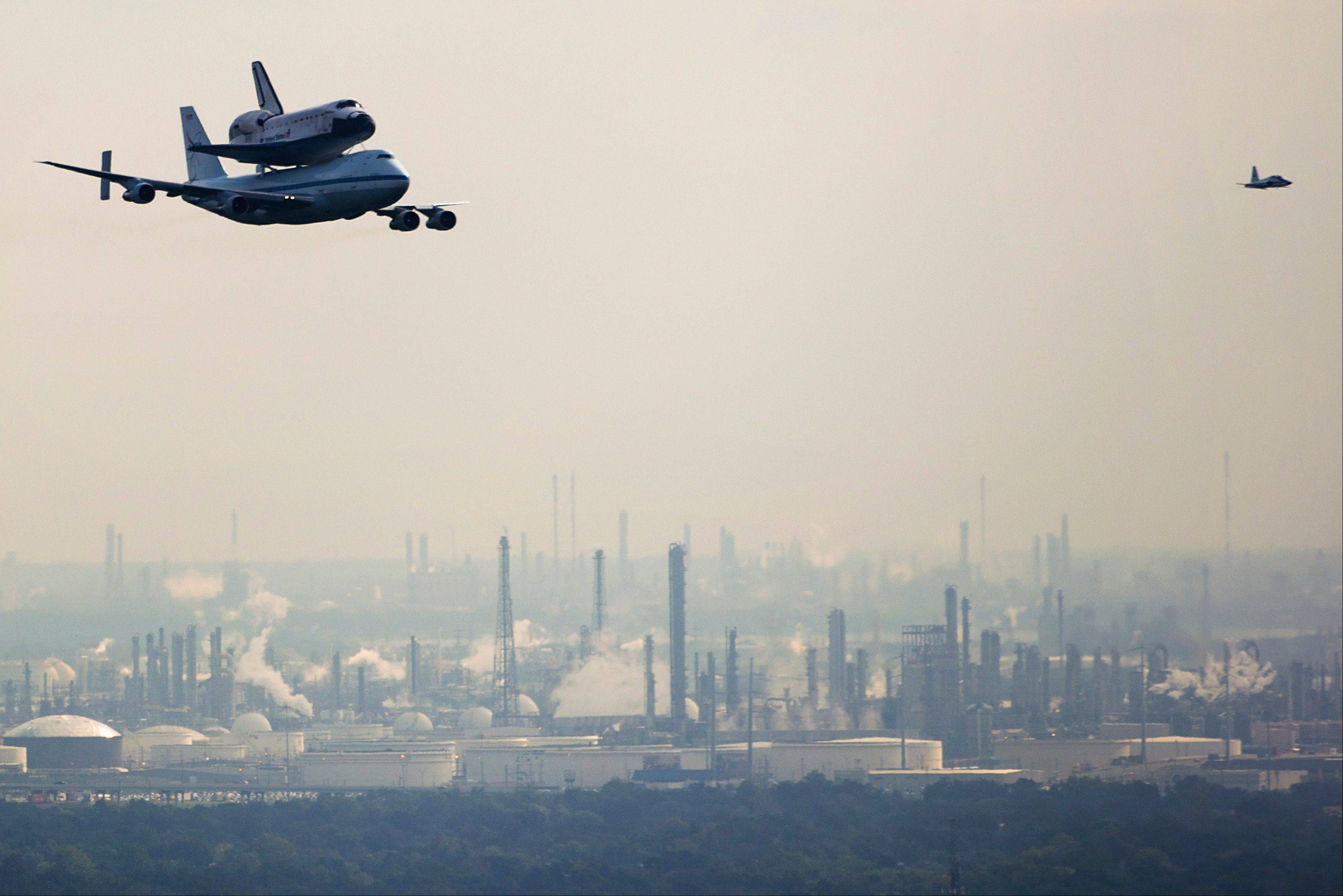 The space shuttle Endeavour, carried atop NASA's 747 Shuttle Carrier Aircraft, passes over petrochemical facilities on the Houston Ship Channel during a flyover on Wednesday, Sept. 19, 2012, in Houston. Endeavour stopped in Houston on its way from the Kennedy Space Center to the California Science Center in Los Angeles, where it will be placed on permanent display.