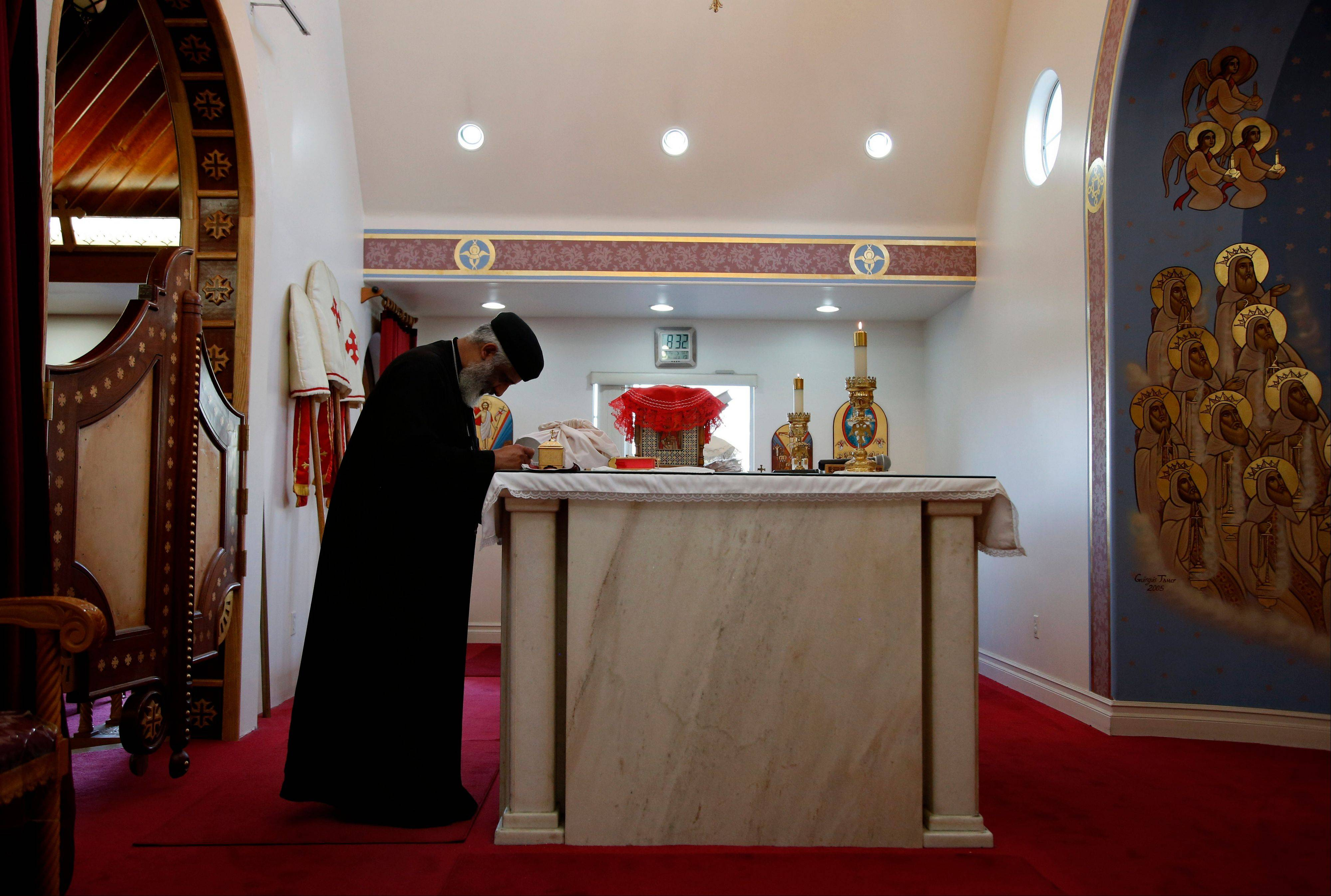 The Rev. Joseph Boules, left, prays during a mass at St. Mary and St. Verena Orthodox Coptic Church in Anaheim, Calif.