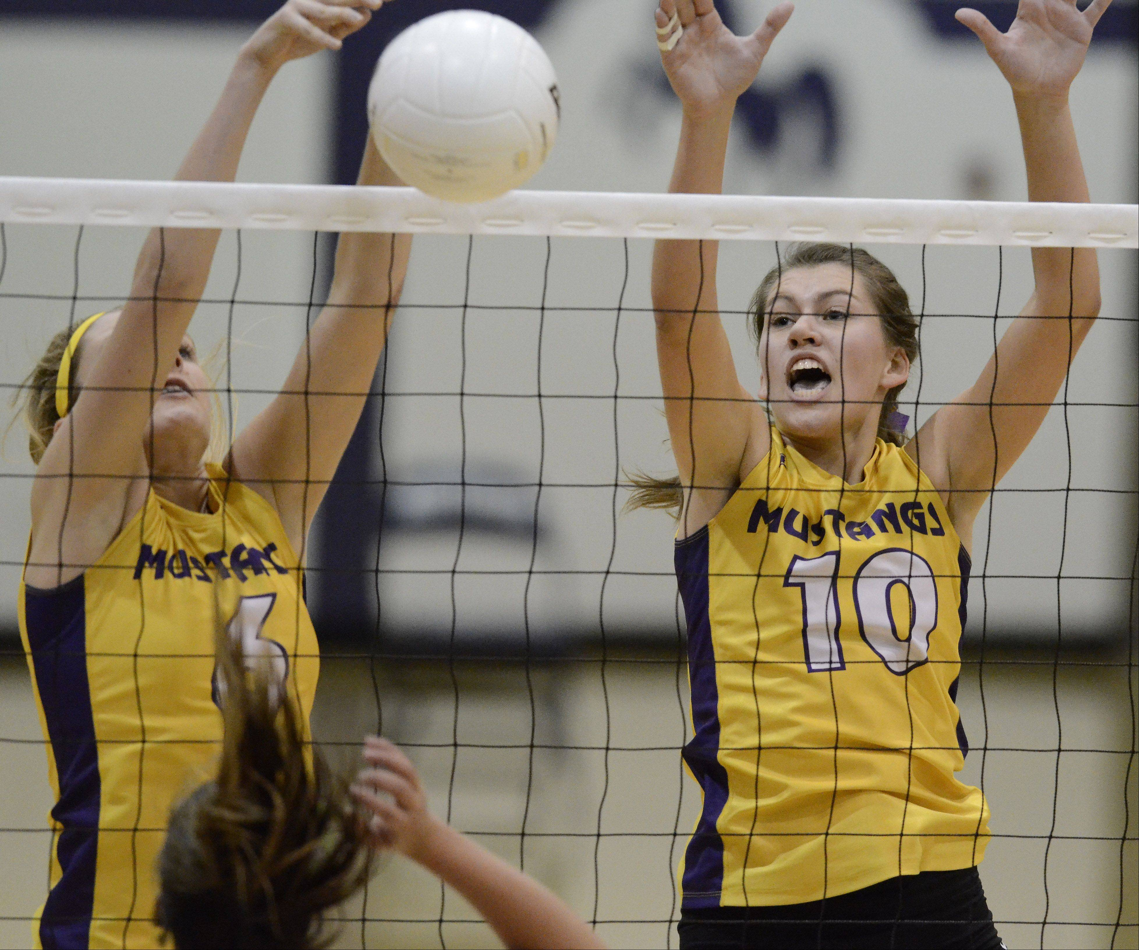 Rolling Meadows' Jenny Vliet, left, and Rachel Mickey block a ball at the net against Buffalo Grove.