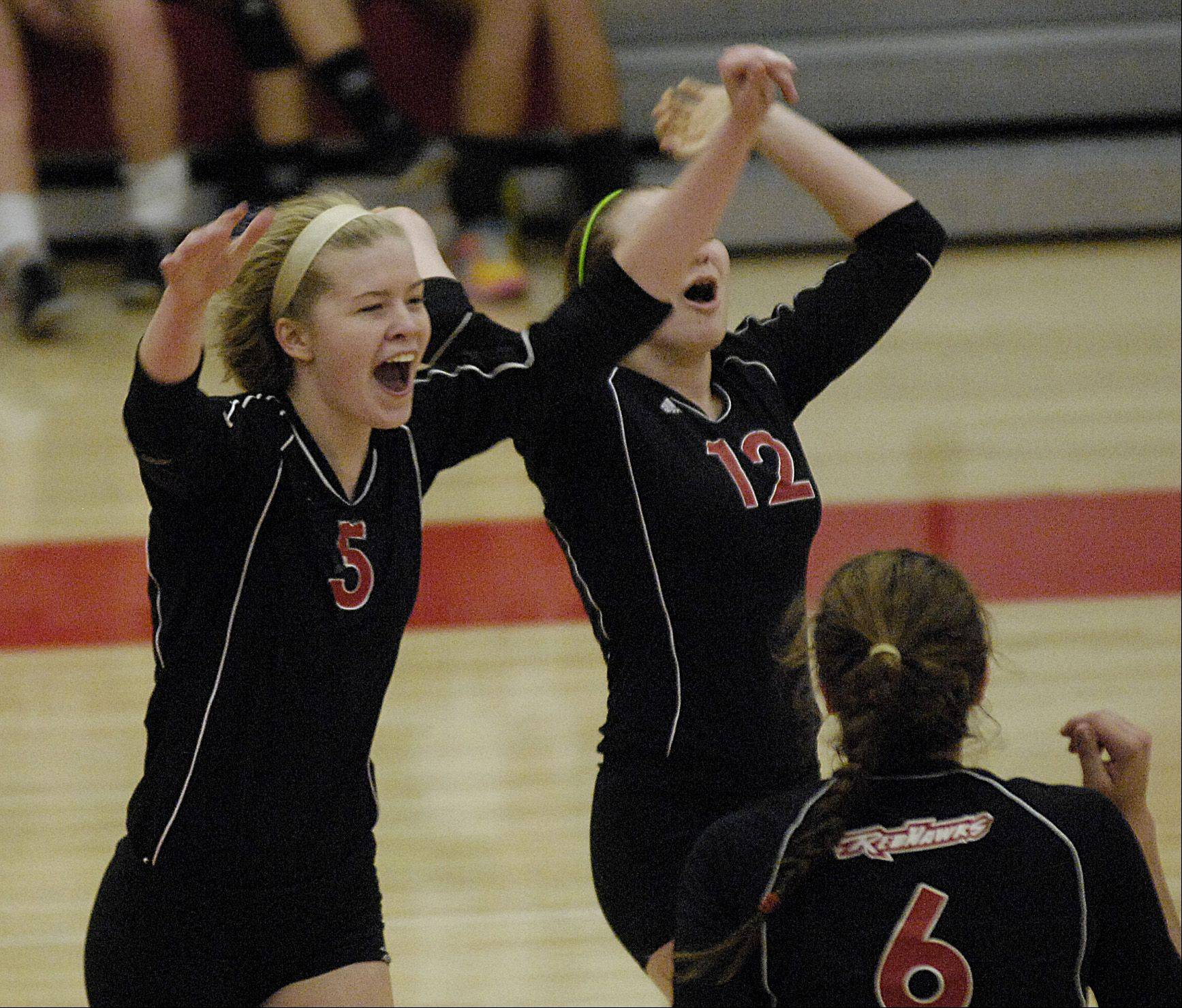 Sammy Condon and Abbi Williamson of Naperville Central celebrate a point against Naperville North at home, Thursday.