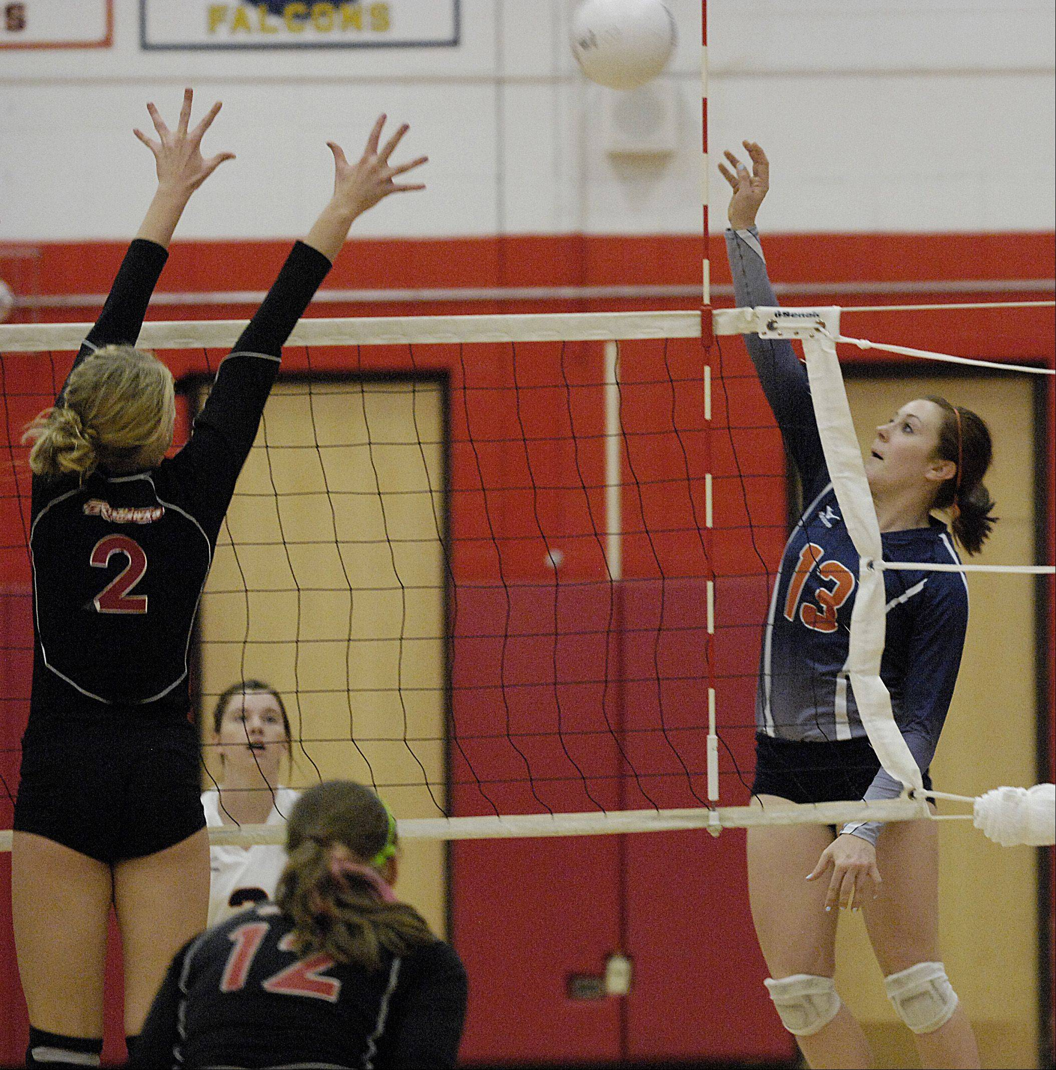 Phoebe Havenaar of Naperville Central jumps to block as shot by Corinne Gajcak of Naperville North at home, Thursday.