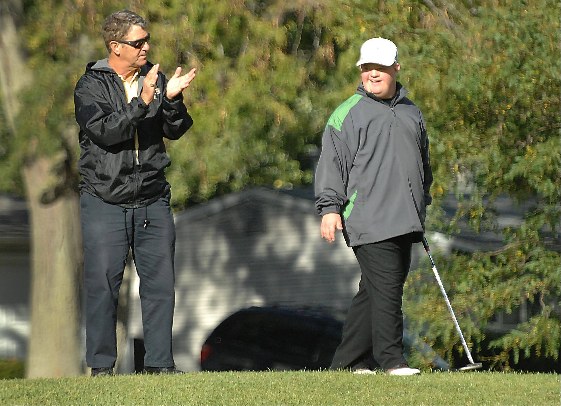 Coach George Rosner applauds and encourages Danny Orlando, who has Down syndrome, as he walks to the green to putt at Streamwood Oaks Golf Club. Danny plays for the Streamwood High School boys team.