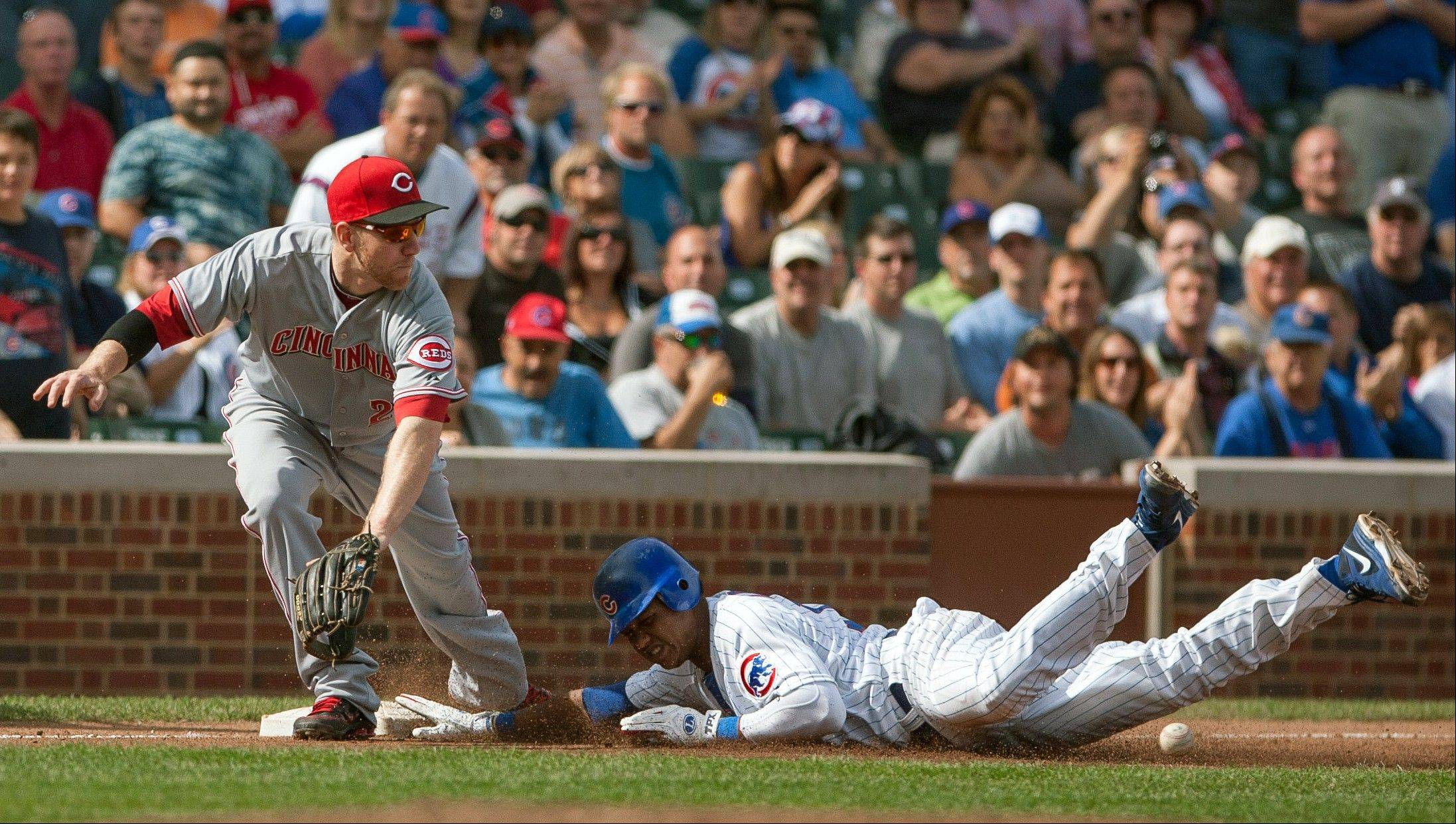 Cubs shortstop Starlin Castro beats the ball to third with a triple Thursday during the fourth inning as Cincinnati Reds third baseman Todd Frazier reaches for the throw at Wrigley Field.